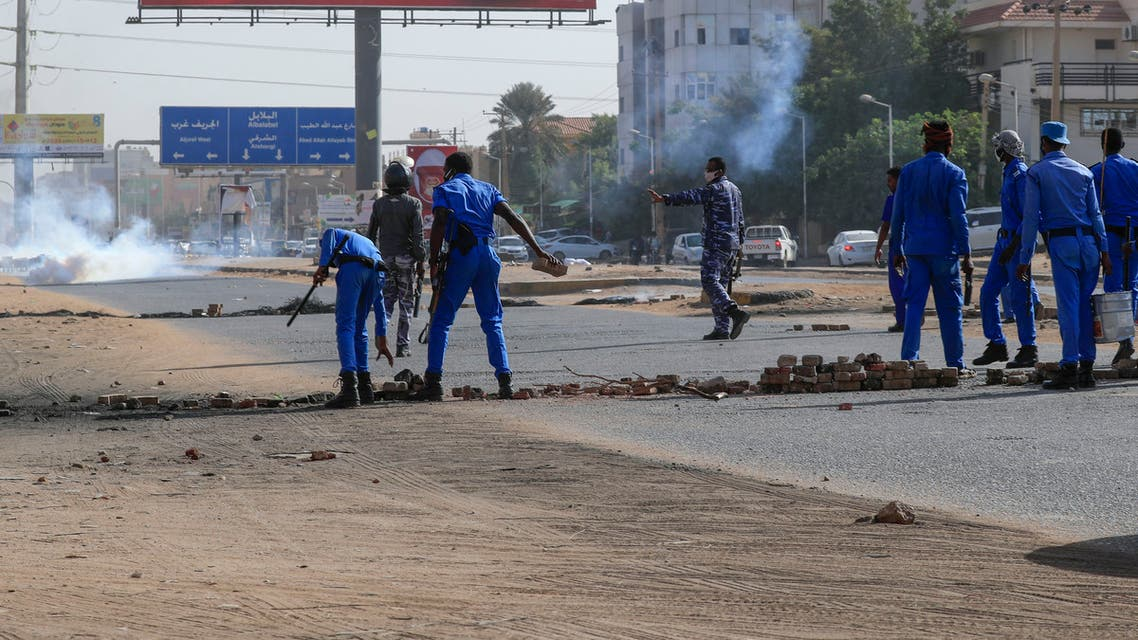 Members of Sudanese security forces remove obstacles placed by protesters as tear gas fumes billow during a demonstration against rising prices, on the main al-Sittin (sixty) road in the capital Khartoum, on January 24, 2021.