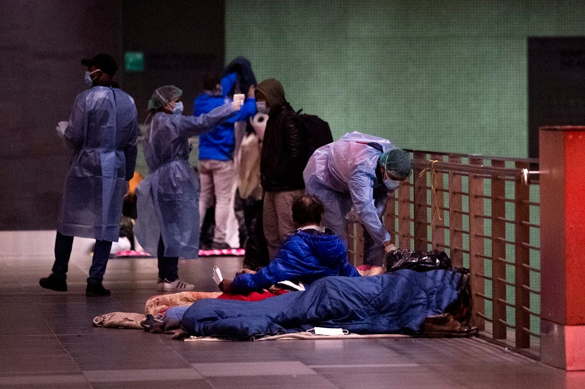 A doctor (Rear R) from MEDU organization (Doctors for Human Rights) performs a temperature scanning on a homeless man (Bottom Front) as doctors roam across the Tiburtina train station on November 25, 2020 in Rome, as part of a MEDU mobile team series of free health checks. (Tiziana Fabi/AFP)