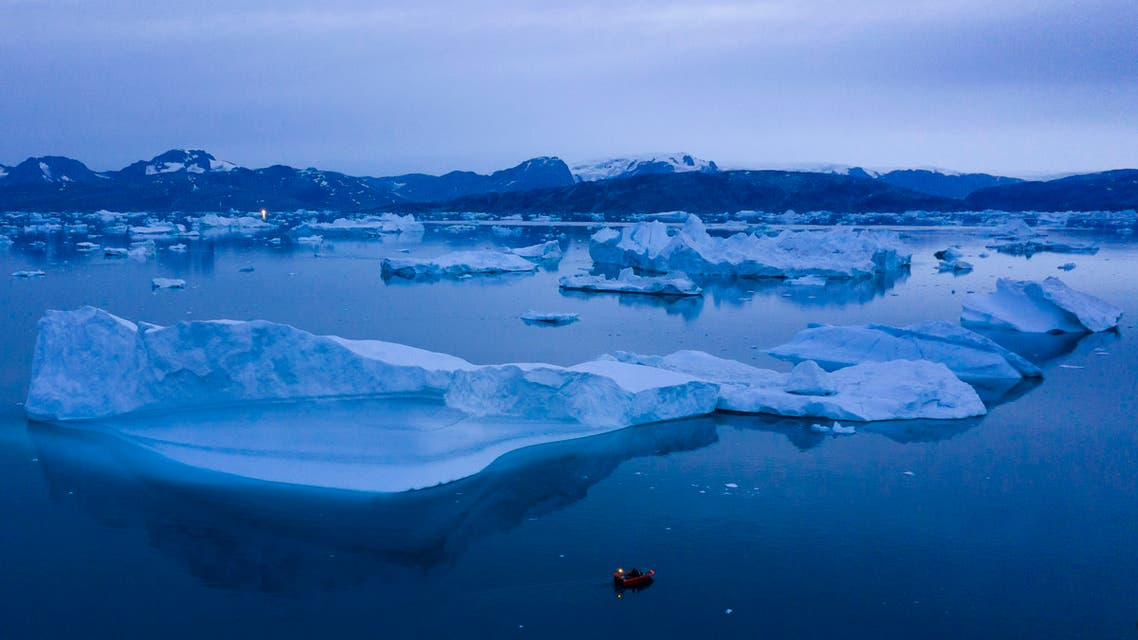 A boat navigates at night next to large icebergs near the town of Kulusuk, in eastern Greenland. (AP)