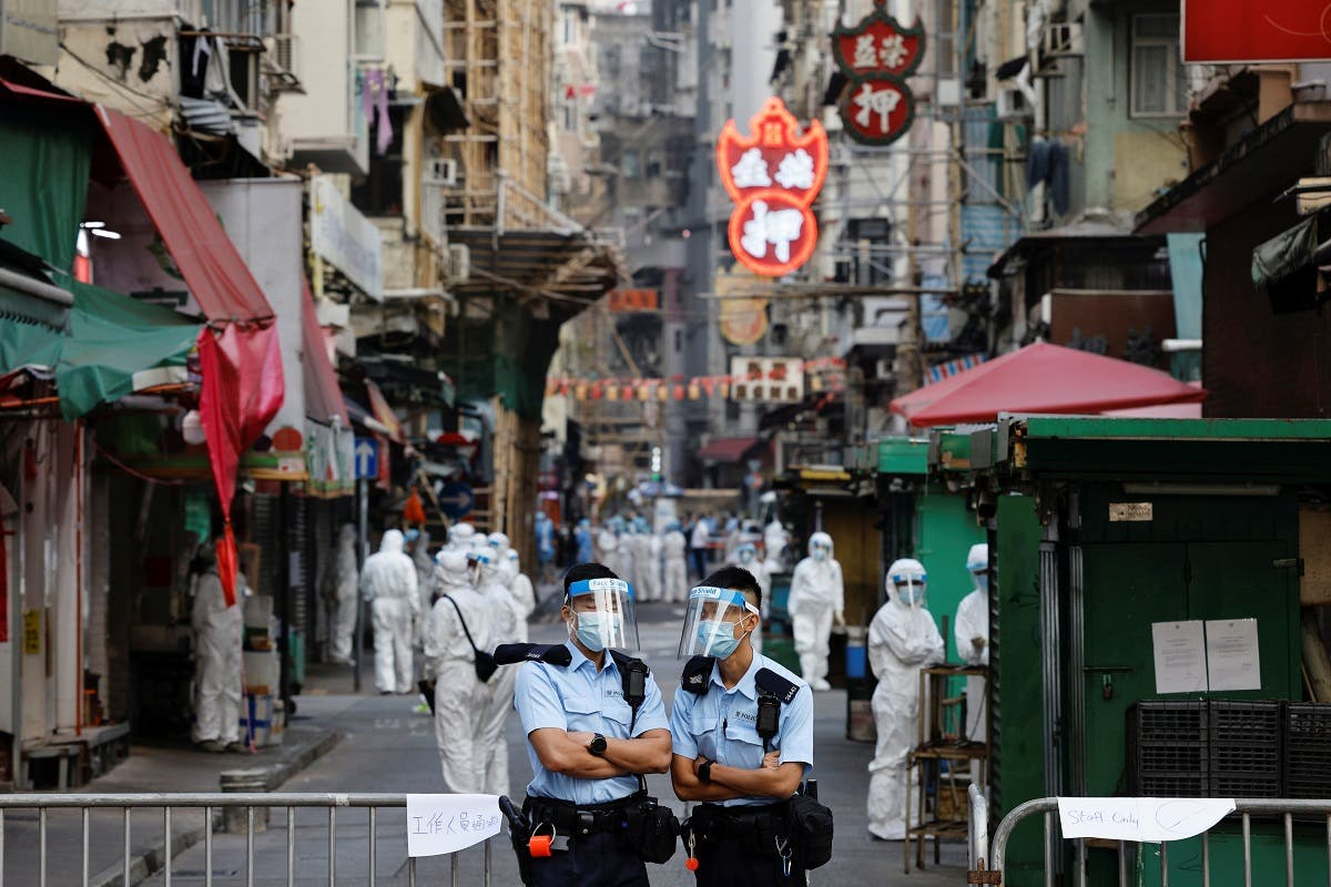 Police and health workers stand in protective gear inside a locked down portion of the Jordan residential area to contain a new outbreak of the coronavirus disease (COVID-19), in Hong Kong, China January 23, 2021. (Reuters)