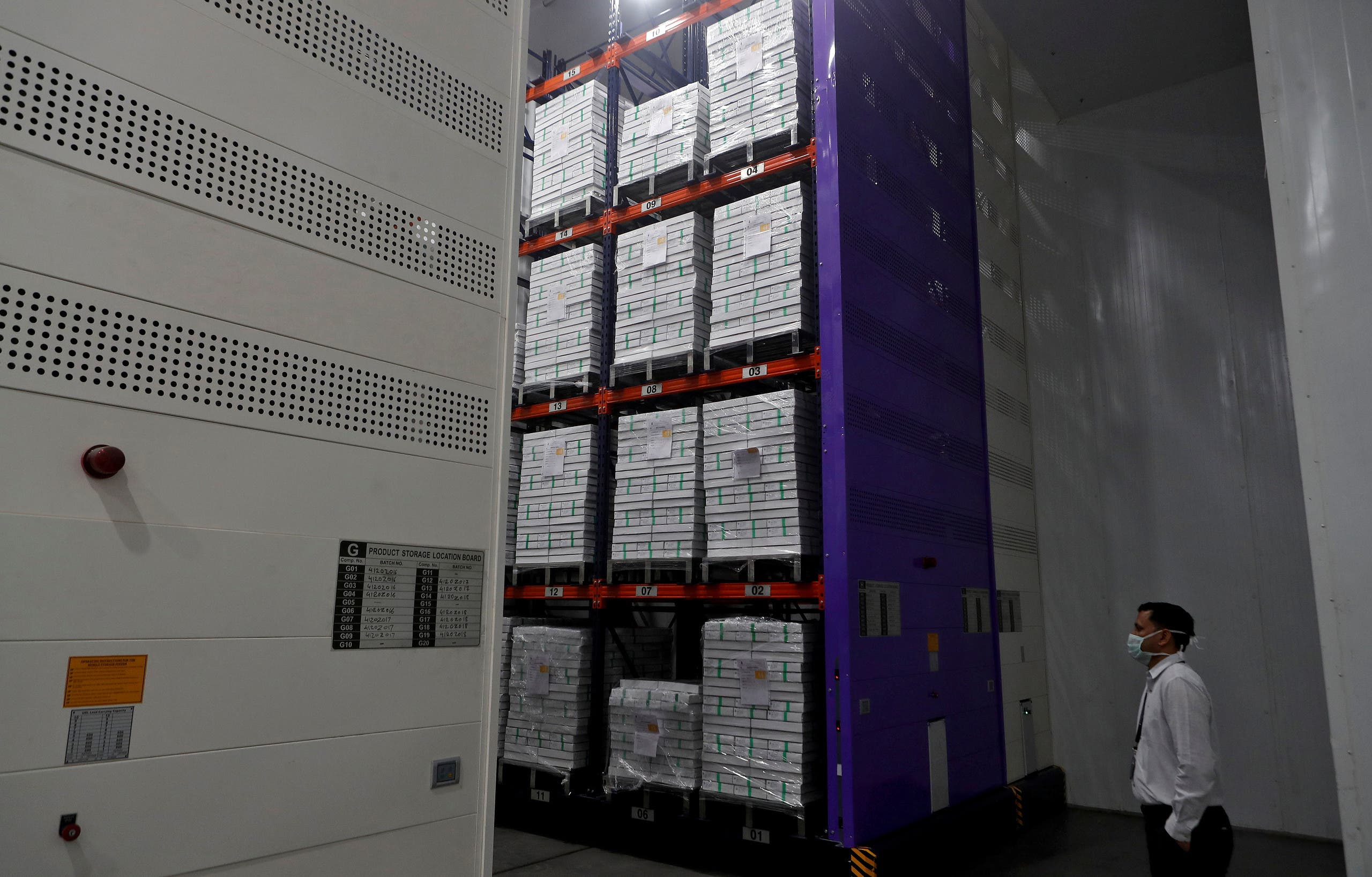 A man wearing a protective mask stands next to boxes containing the vials of AstraZeneca's COVISHIELD, coronavirus disease (COVID-19) vaccine, inside a cold room at the Serum Institute of India, Pune, India, on November 30, 2020. (Reuters)