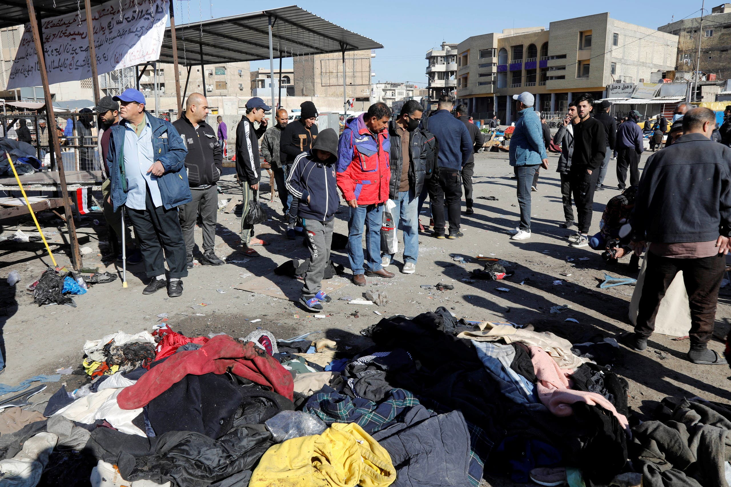 People gather at the damaged site in the aftermath of a twin suicide bombing attack in a central market, in Baghdad, Iraq January 22, 2021. (Reuters/Khalid al-Mousily)