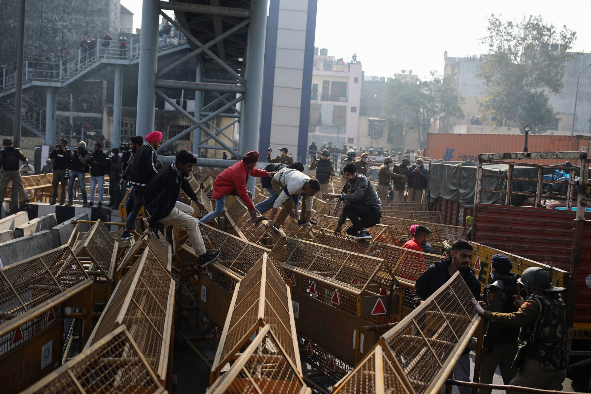 Protesting farmers jump police barricades tp march to the capital during India's Republic Day celebrations in New Delhi, India, Tuesday, Jan.26, 2021. (AP)