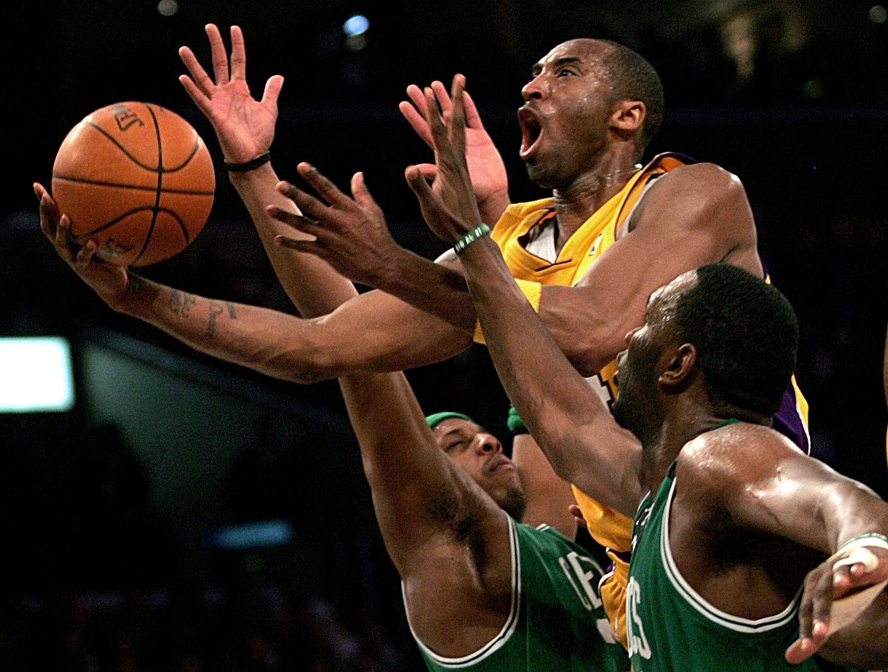 Kobe Bryant, top, goes up for a shot between the Boston Celtics' Paul Pierce, left, and Al Jefferson during the first half of an NBA basketball game in Los Angeles, Feb. 23, 2006. (AP)