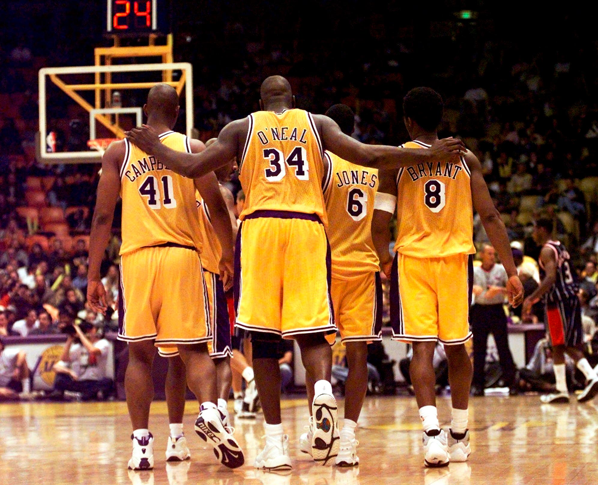 In this Feb. 5, 1999, file photo, Los Angeles Lakers center Shaquille O'Neal (34) puts his arms around teammates, Elden Campbell (41) and Kobe Bryant (8) as Eddie Jones (6) and Derek Harper . (AP)