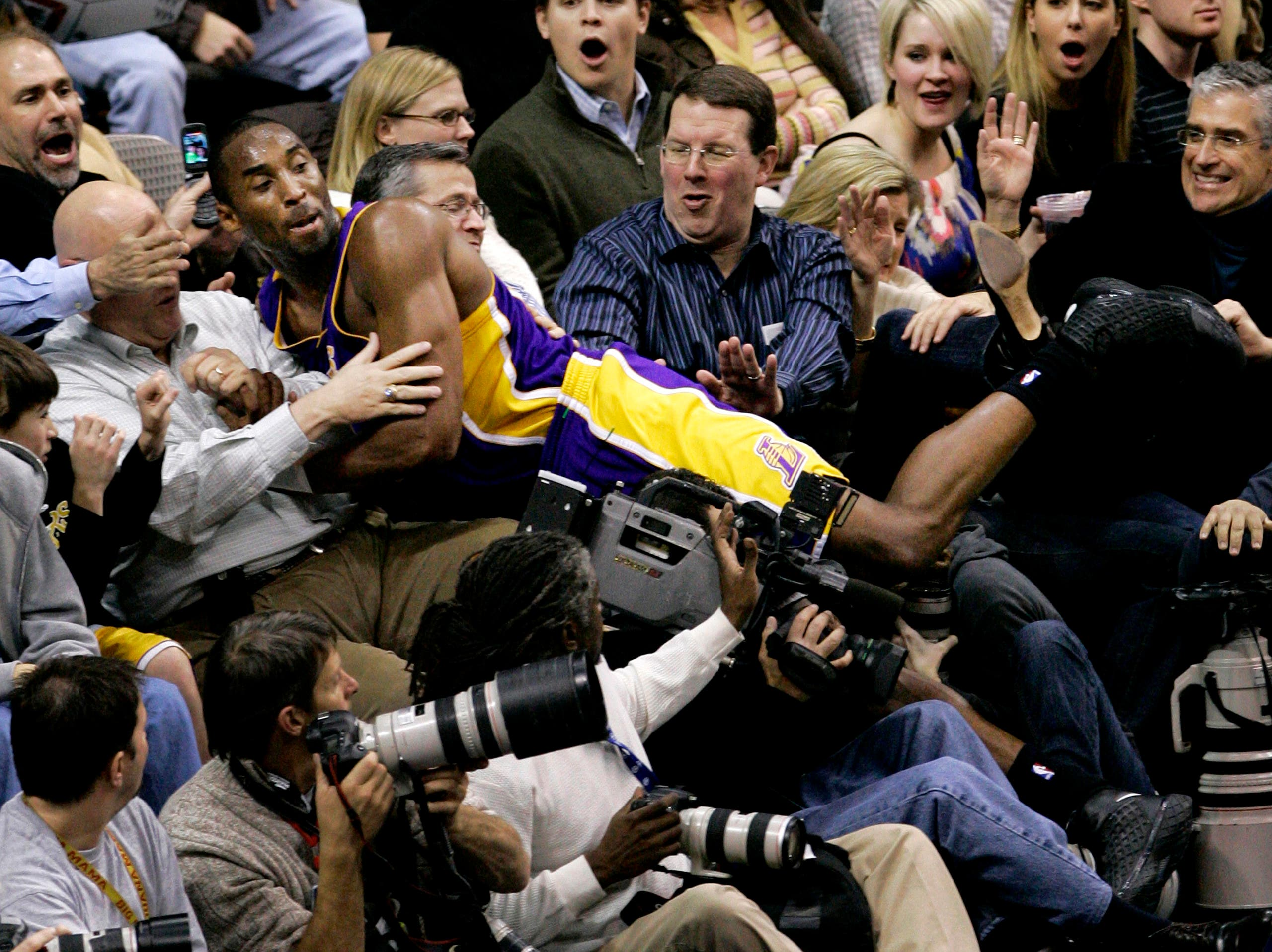 Kobe Bryant lands amongst fans after chasing down a loose ball in the second half of an NBA basketball game against the Dallas Mavericks in Dallas, Friday, Jan. 25, 2008. (AP)