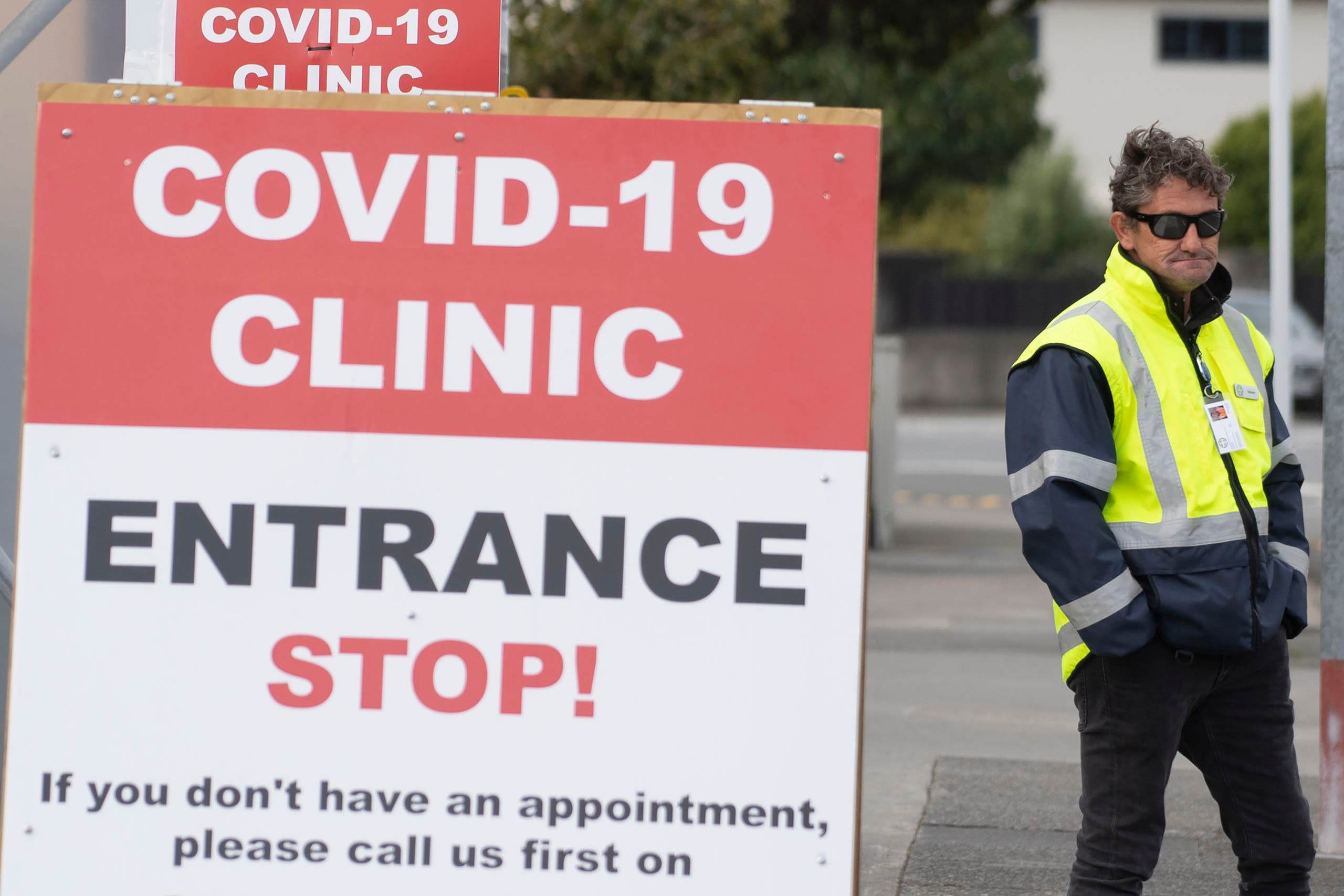 This file photo taken on April 20, 2020 shows a security guard standing outside a COVID-19 coronavirus clinic in Lower Hutt, near Wellington.