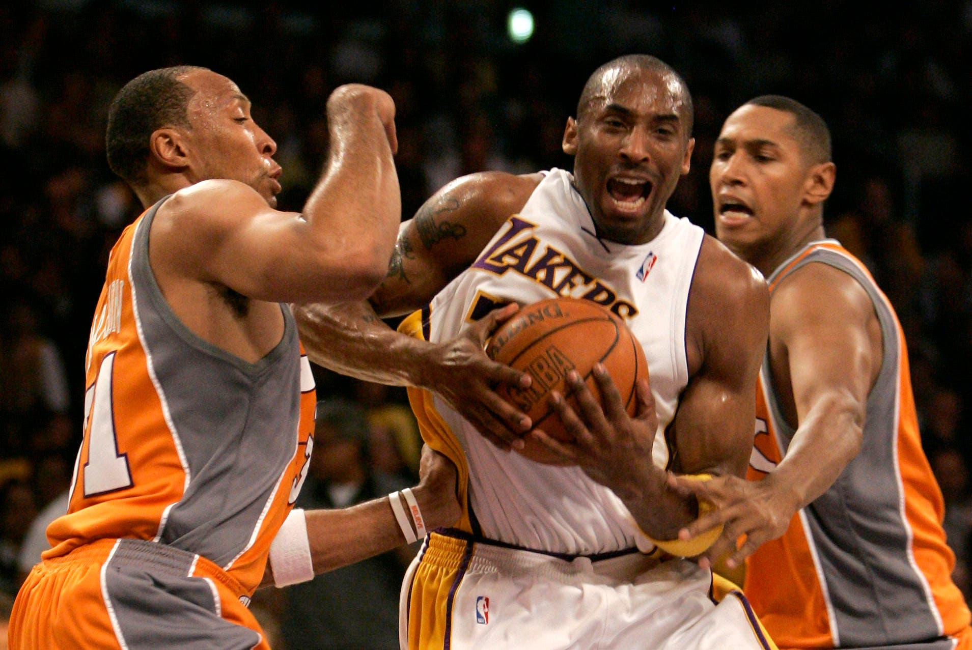 Kobe Bryant, center, is guarded by Phoenix Suns' Shawn Marion, left, and Boris Diaw during the first half of their Western Conference playoff basketball game in Los Angeles, Sunday, April 29, 2007. (AP)