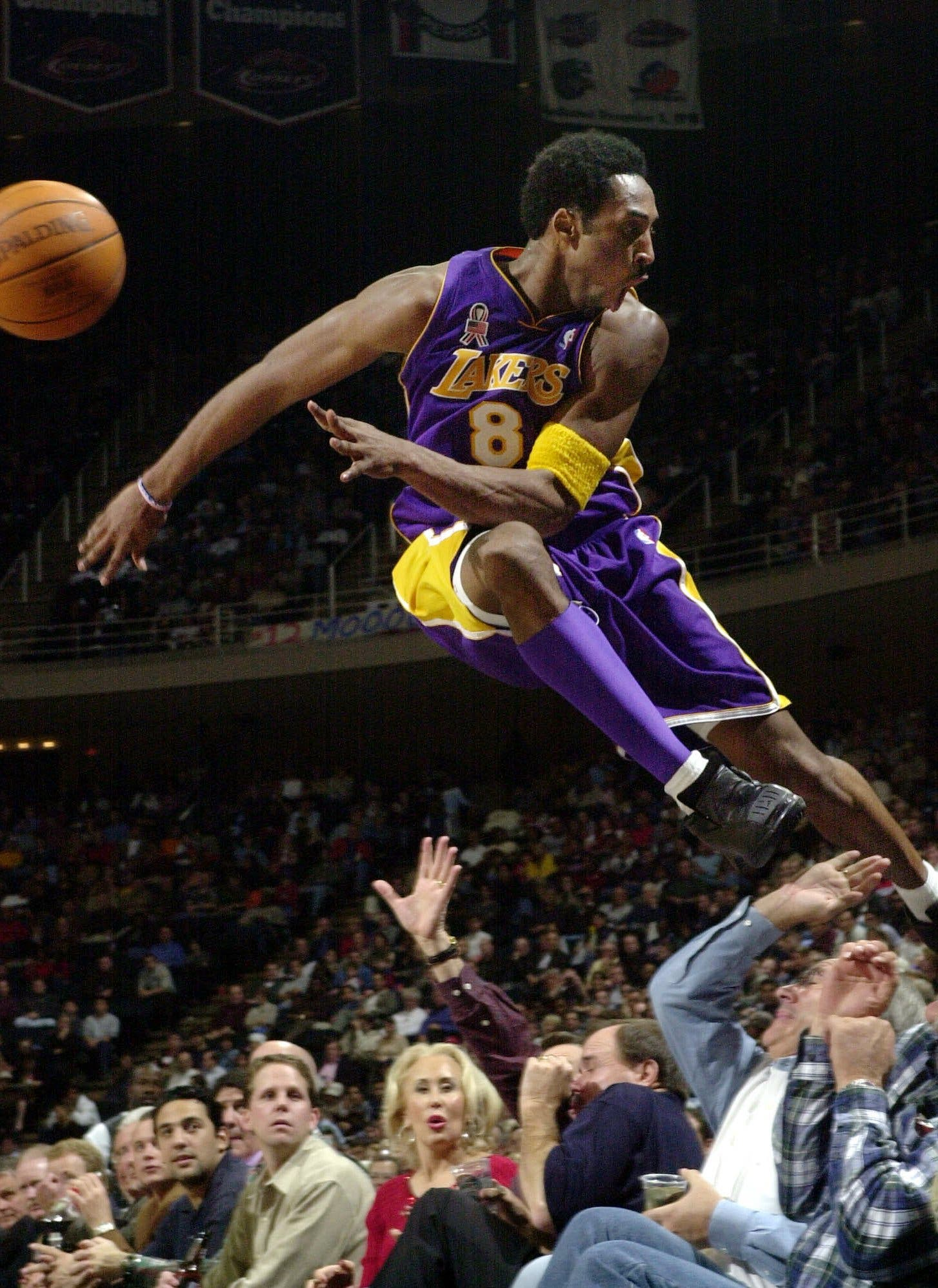 Kobe Bryant jumps over a row of fans after saving the ball from going out of bounds in the second half of the Lakers 107-101 win over the Houston Rockets Thursday, Dec. 20, 2001. (AP)