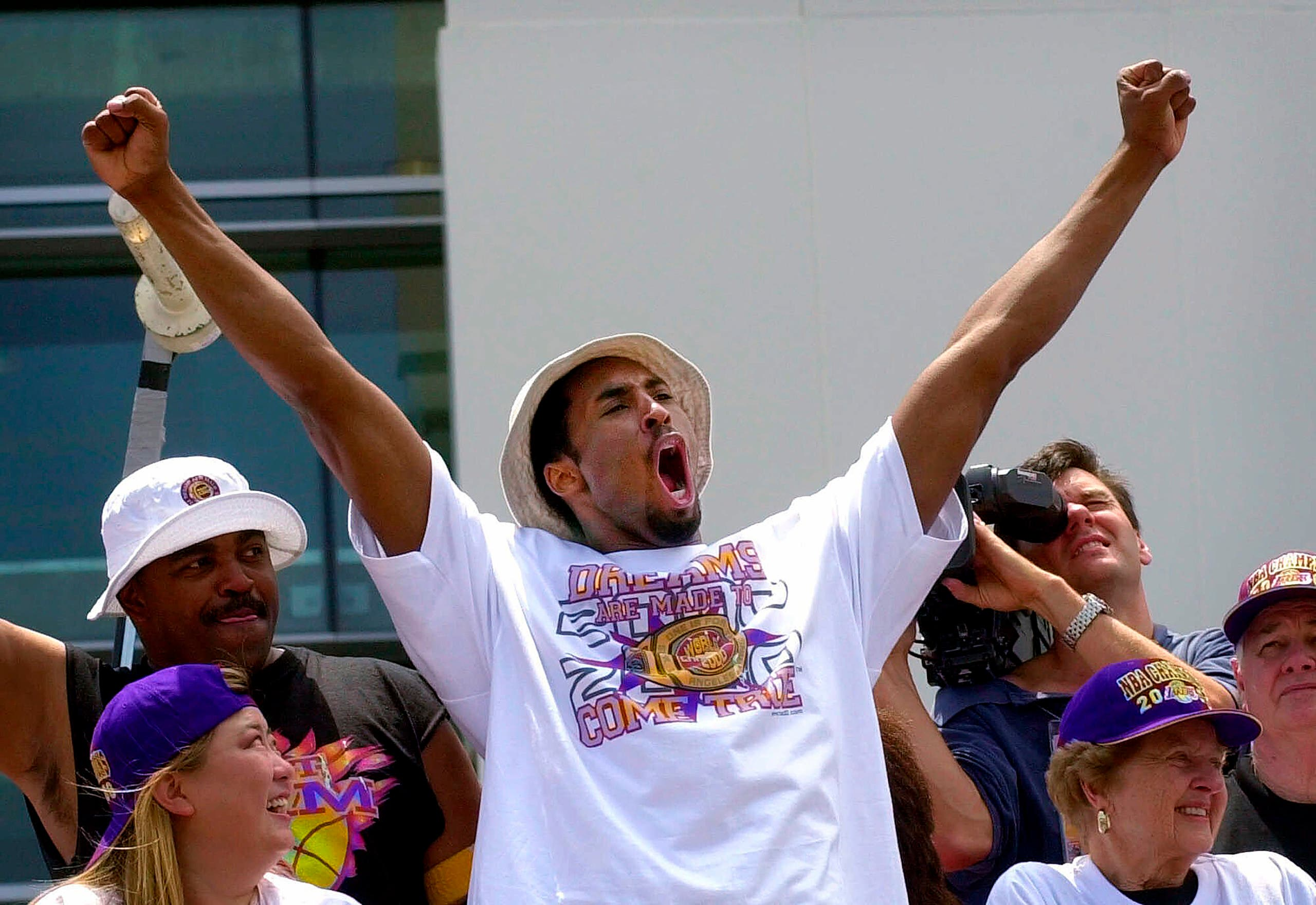 Kobe Bryant gestures to the crowd from atop a doubledecker bus as the Lakers victory parade arrives at Staples Center in Los Angeles, June 21, 2000. (AP)