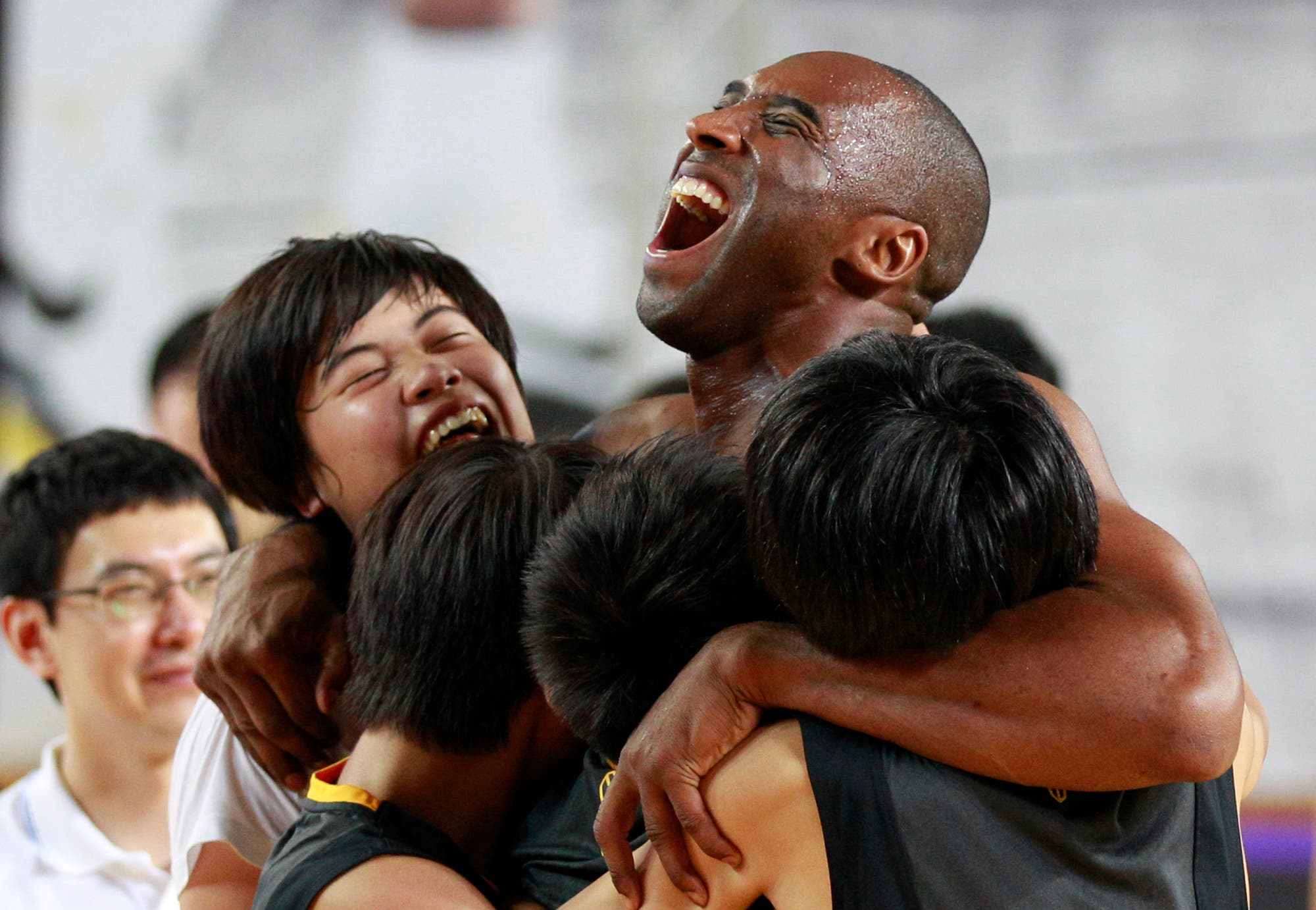 Kobe Bryant embraces South Korean students in his basketball clinic for youth in Seoul, South Korea. (AP)