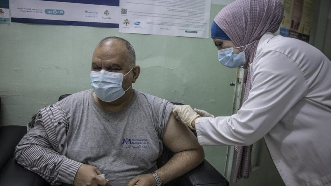 A medical worker administers a dose of COVID-19 vaccine at the Irbid Vaccination Clinic in Jordan.  © UNHCR/Jose Cendon