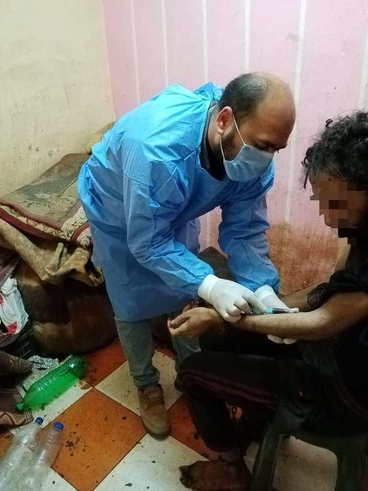 ممرض يأخذ عينة من دم الشاب لفحصها