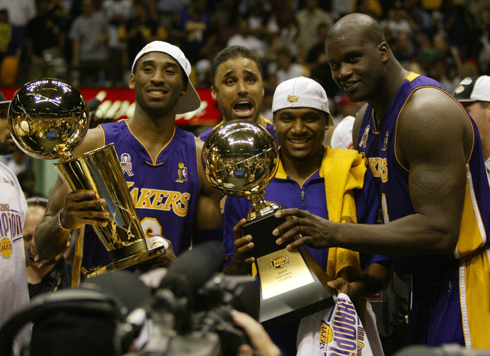 Los Angeles Lakers Kobe Bryant, left, holding the championship trophy, celebrates with teammates Rick Fox, Lindsey Hunter, second from right, and Shaquille O'Neal, right, holding the MVP trophy, after winning Game 4 of the NBA Finals, Wednesday, June 12, 2002, in East Rutherford, N.J. (AP)