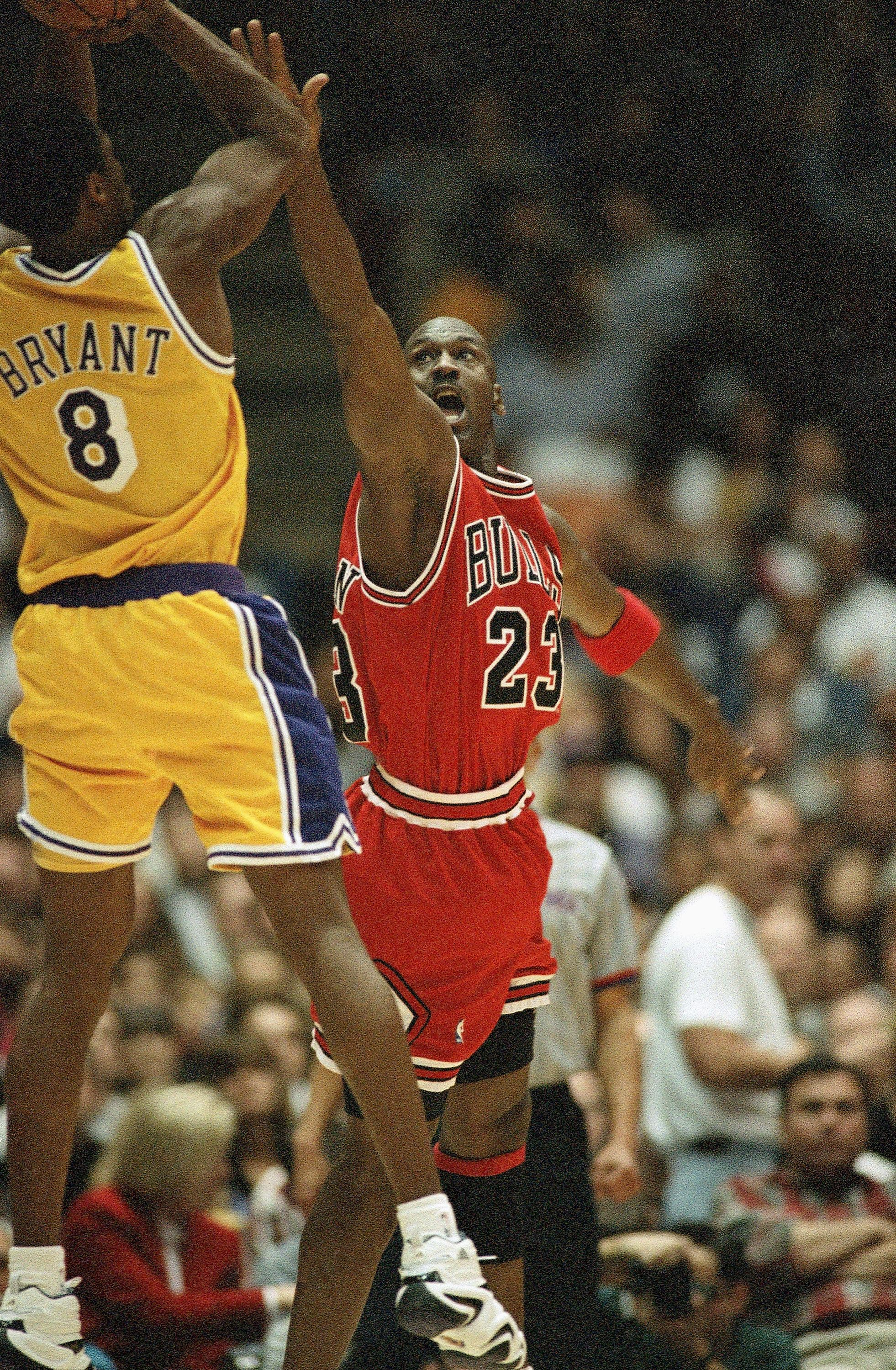 Chicago Bulls Michael Jordan (23) reaches to defend against Los Angeles Lakers Kobe Bryant (8) during the second quarter action, Feb. 1, 1998. (AP)