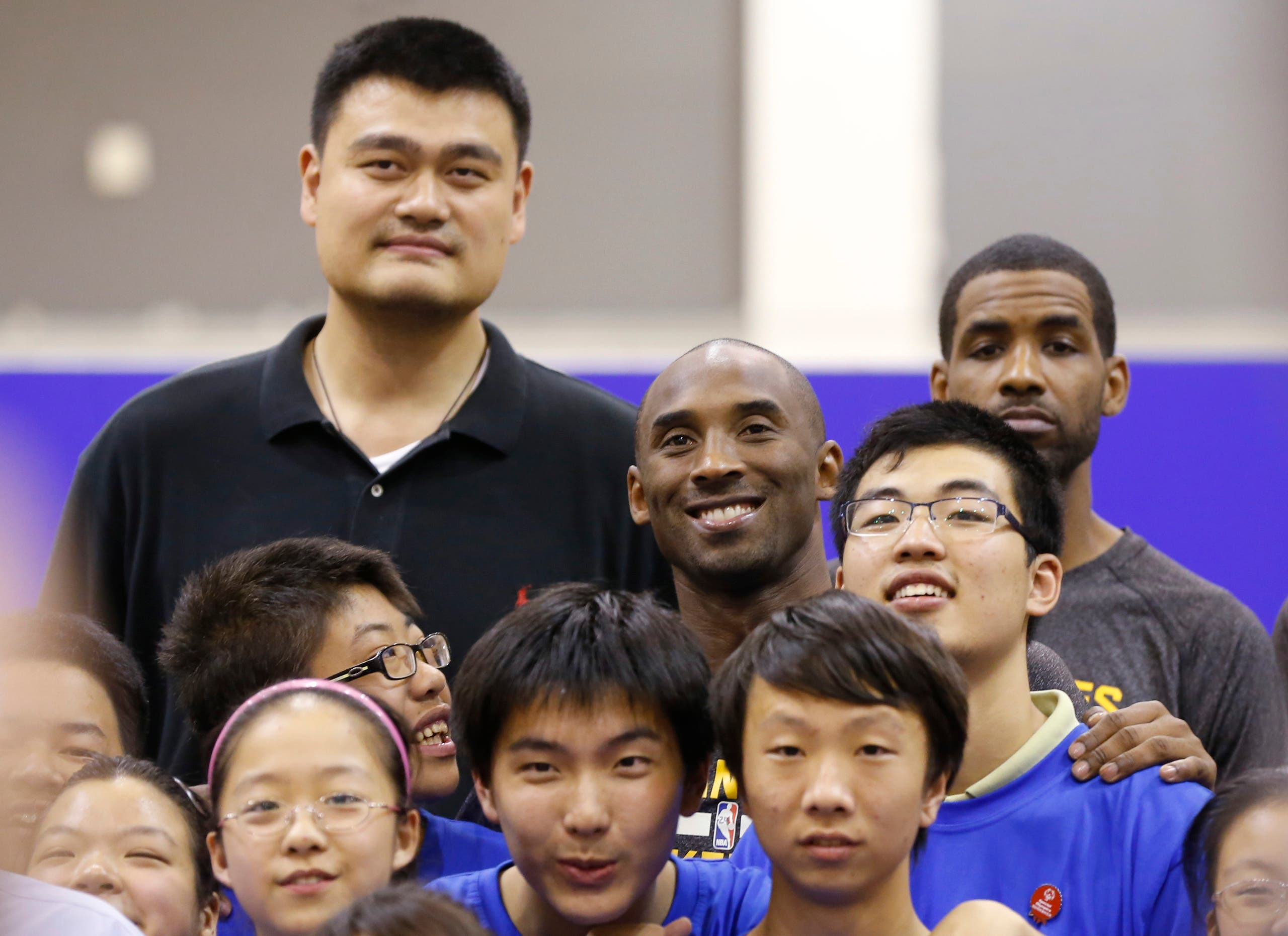 Kobe Bryant of the Los Angeles Lakers, top center, former NBA Houston Rockets basketball player Yao Ming, top left, pose with children during the NBA Cares Special Olympics Basketball Clinic in China. (AP)