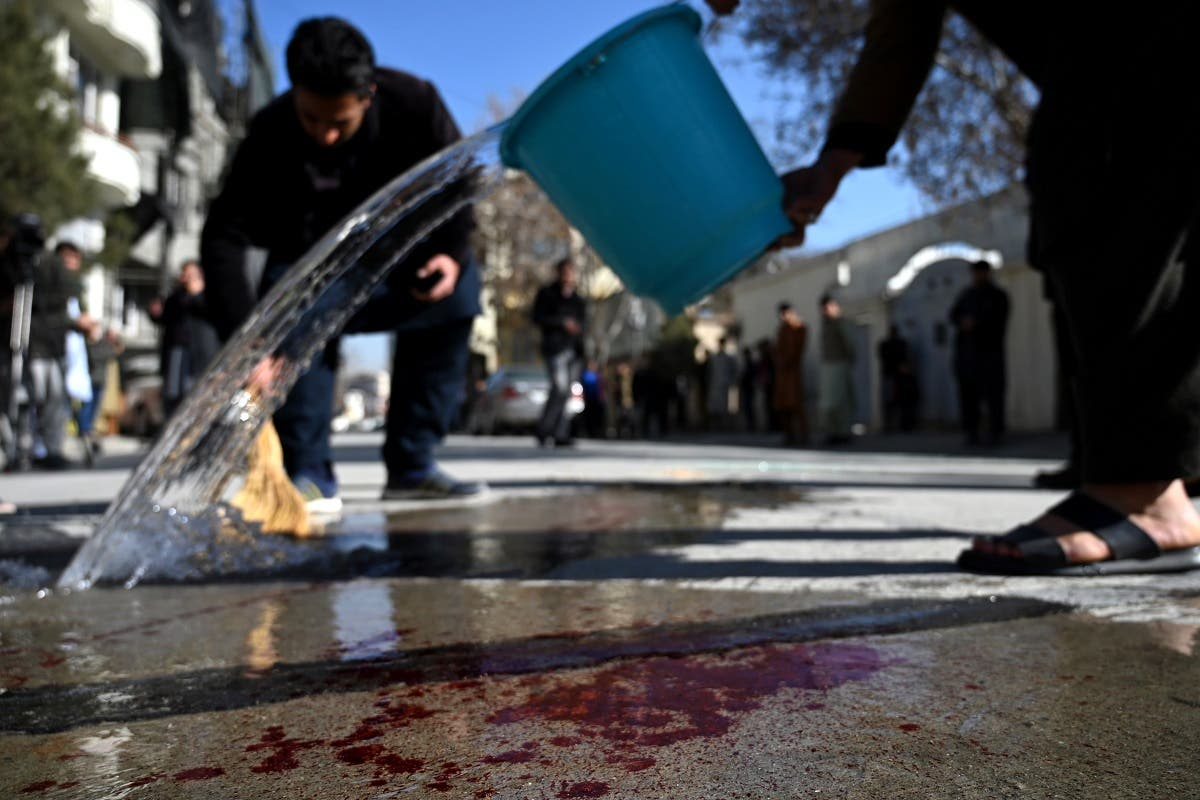Residents wash a road following gunmen shot dead two Afghan women judges working for the Supreme Court, in Kabul on January 17, 2021. (Wakil Kohsar/AFP)