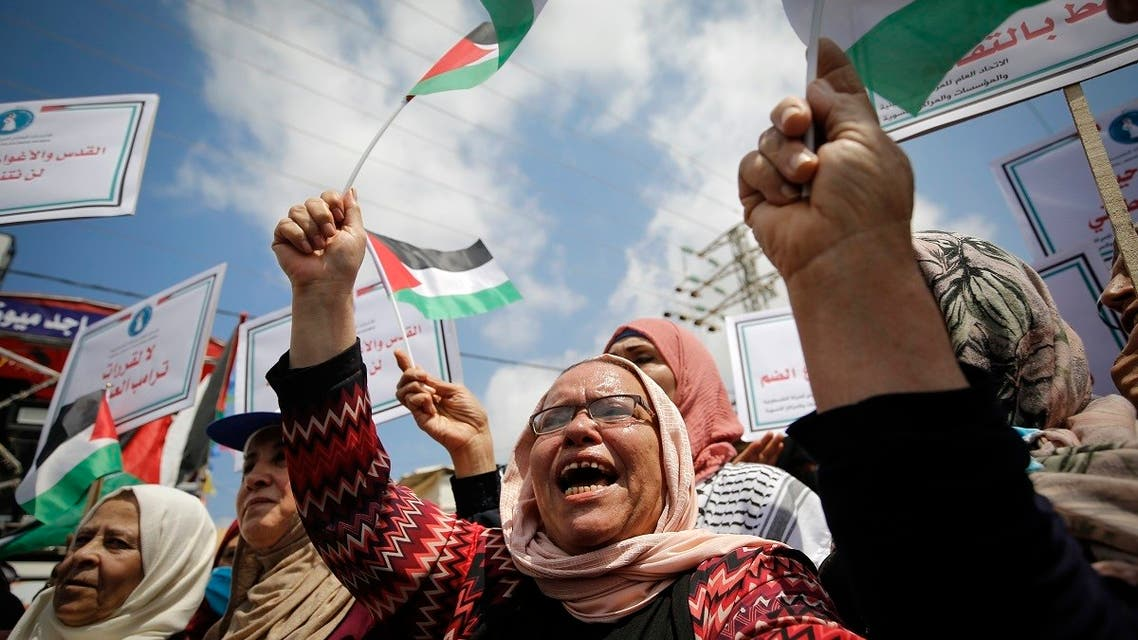 Palestinian women lift national flags and placards during a rally for supporters of the Fateh movement against Israel's West Bank annexation plans, in Beit Hanun in the north of the Gaza Strip, July 6, 2020. (AFP)