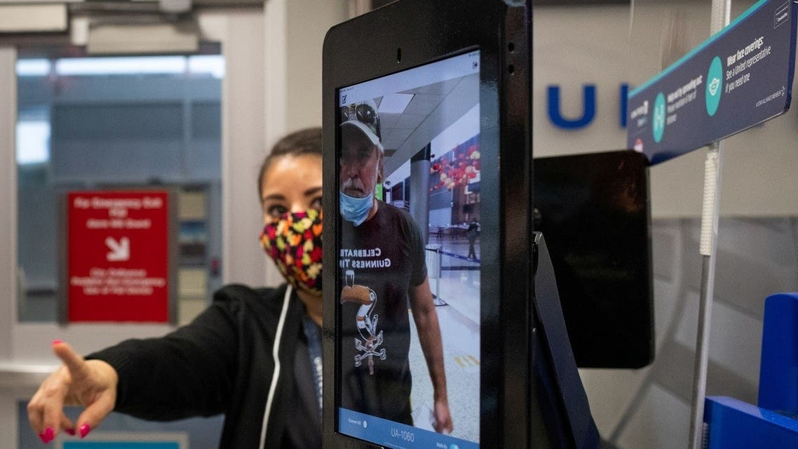A United Airlines employee helps a passenger position himself as he uses biometric boarding to board an international flight from IAH George Bush Intercontinental Airport, July 21, 2020. (Reuters)