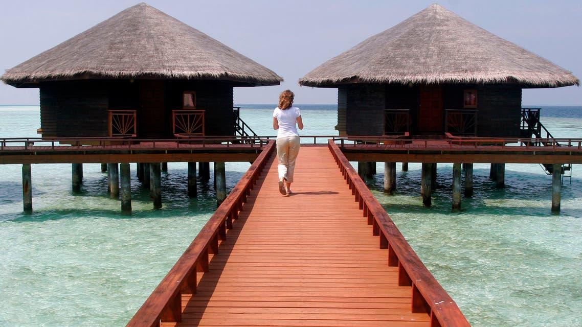 A resort employee walks along the walkway of the Baros Island resort  in the Maldives. AP