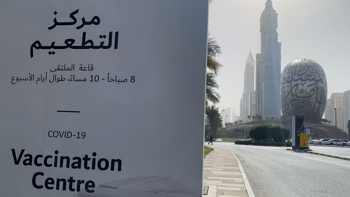 An advertisement placard informs the public of the location of a designated COVID-19 vaccination center at Dubai's financial center district, UAE. (AFP)