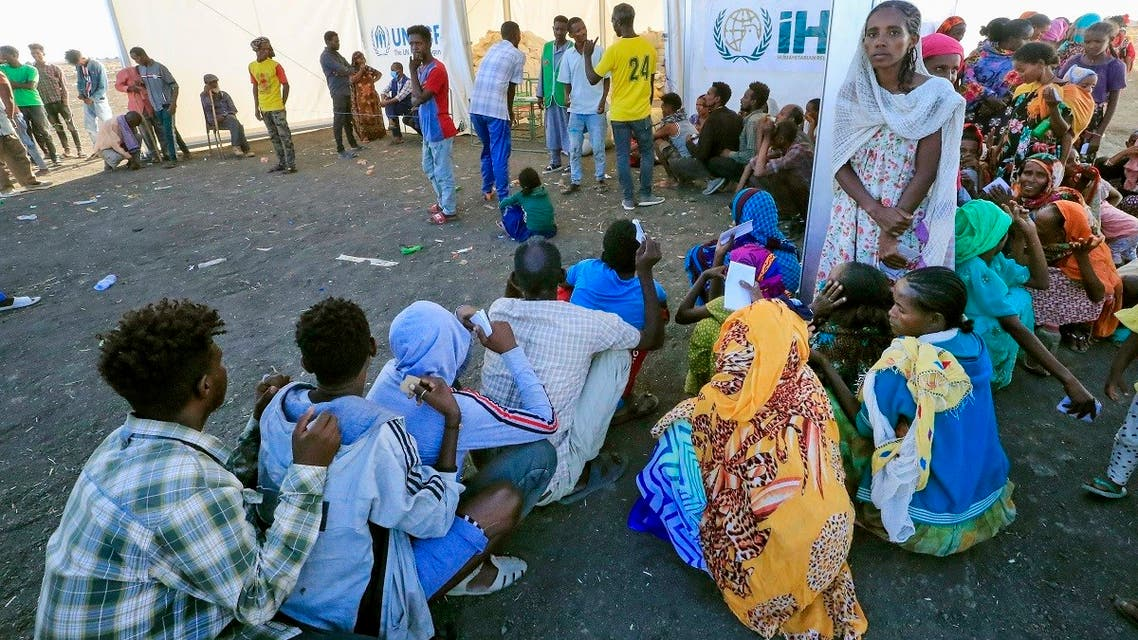 Ethiopian refugees, who fled the Tigray conflict, gather to receive aid at the Tenedba camp in Mafaza, eastern Sudan on January 8, 2021, upon their arrival at the camp from the reception center. (AFP)
