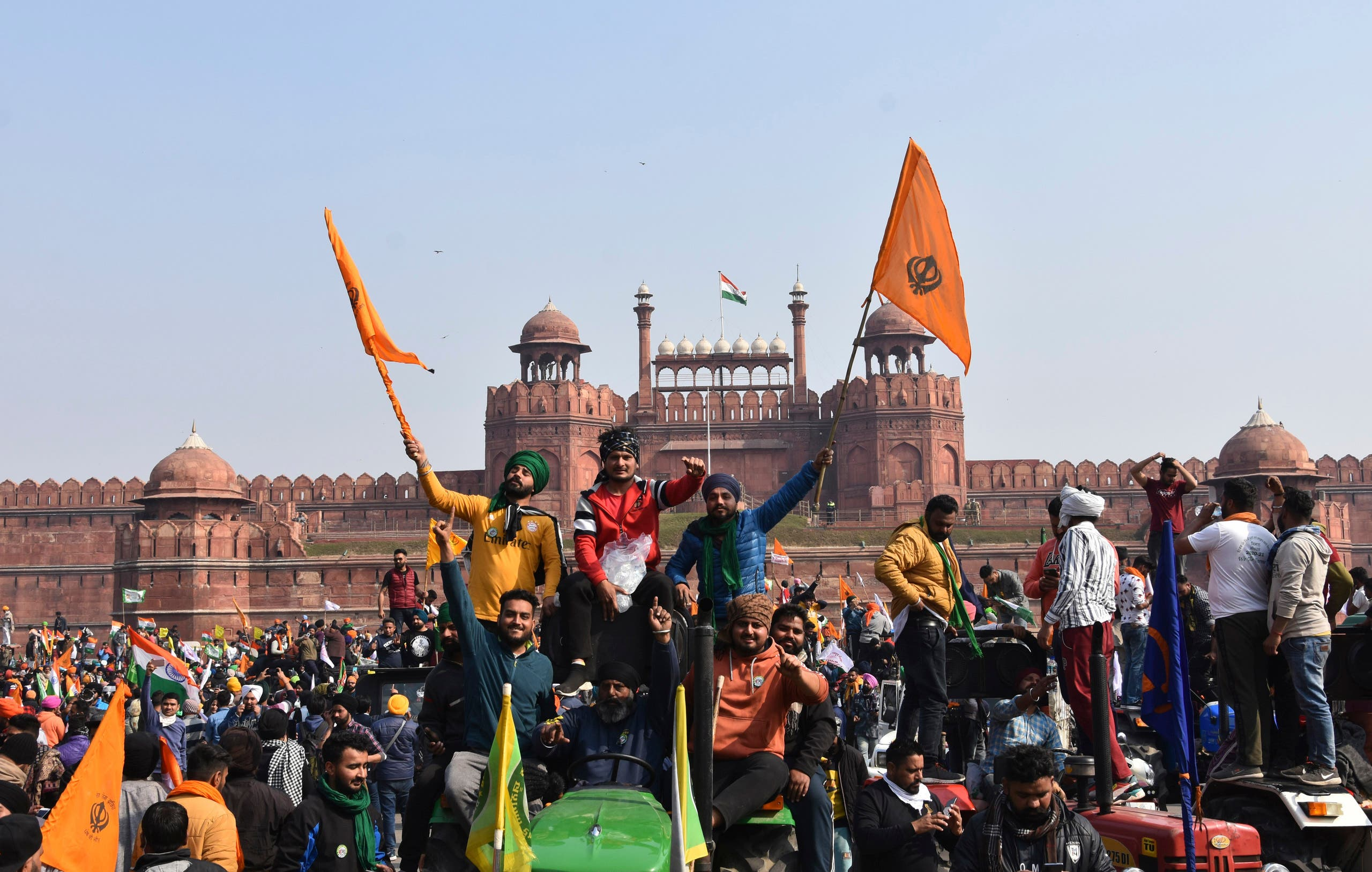 Sikhs hoist a Nishan Sahib, a Sikh religious flag, on a minaret of the historic Red Fort monument in New Delhi, India, Tuesday, Jan. 26, 2021. (AP)