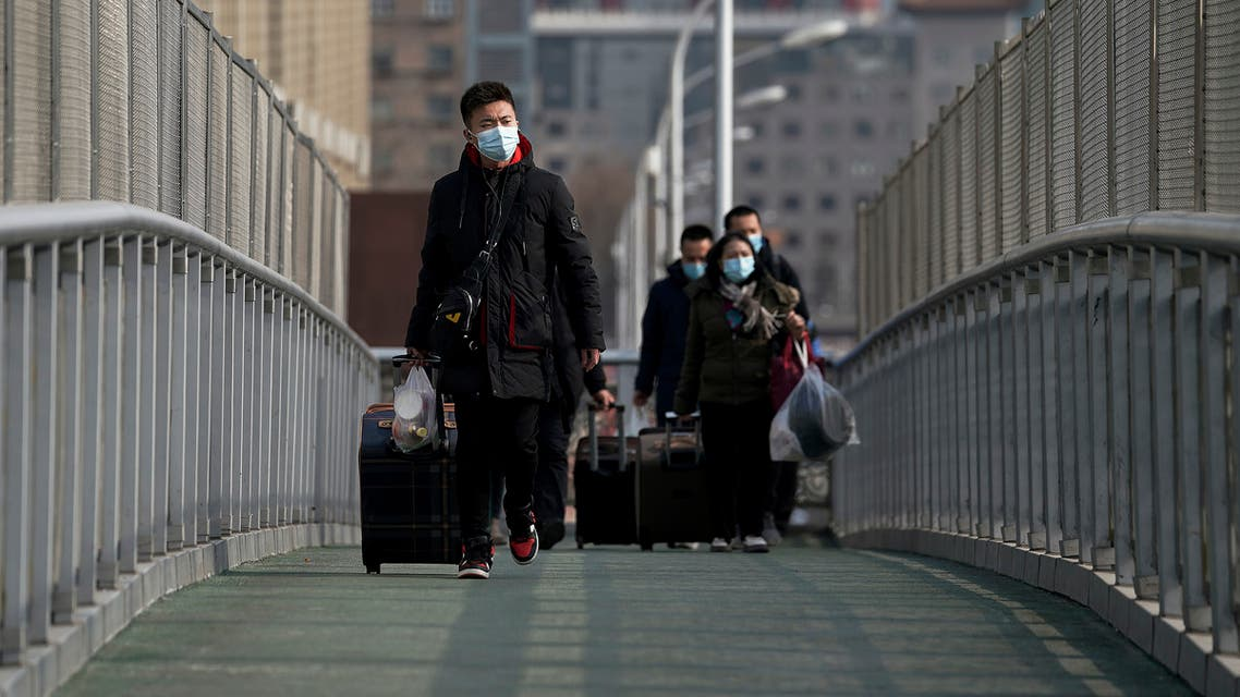 People wearing face masks to help curb the spread of the coronavirus walk with their luggage over a pedestrian bridge to the railway station to catch their trains in Beijing, Wednesday, Jan. 27, 2021. (AP)