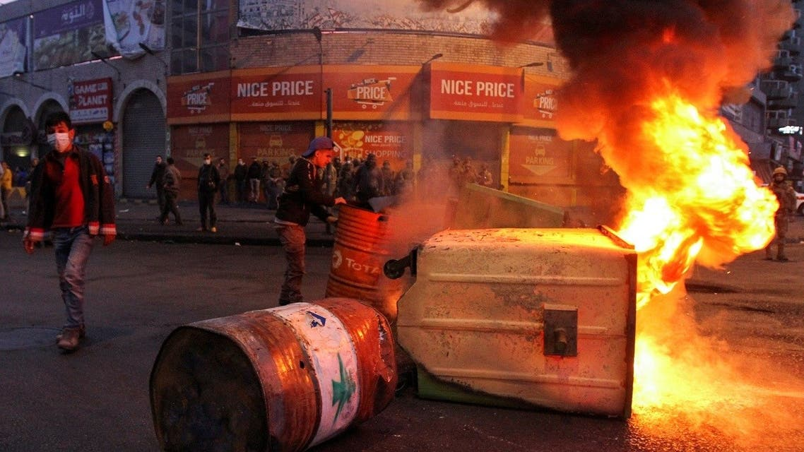 Garbage bins, set on fire by demonstrators, block a road during a protest against the lockdown and worsening economic conditions in Tripoli, Lebanon Jan. 26, 2021. (Reuters)