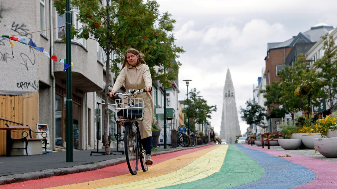 A woman cycles down a street painted in rainbow colours near the Hallgrimskirkja church, as the outbreak of the coronavirus disease (COVID-19) continues, in Reykjavik. (Reuters)
