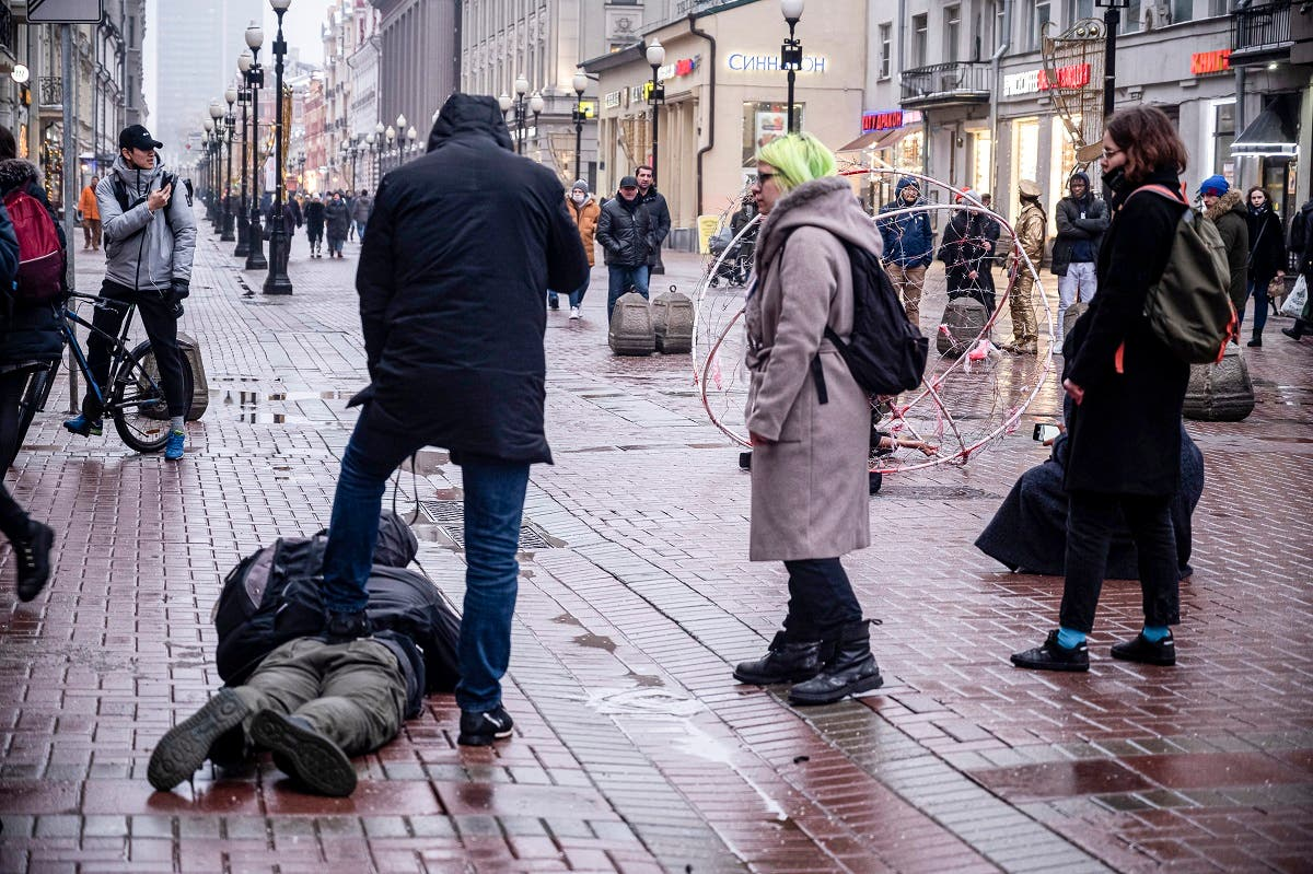 A policeman dressed in civilian clothes holds down a journalist who was filming opposition activist Pavel Krysevich during his action in support of Russian opposition leader Alexei Navalny and against the mass arrests at Saturday's uncoordinated rally in Moscow, Russia, Sunday, Jan. 24, 2021. (AP)