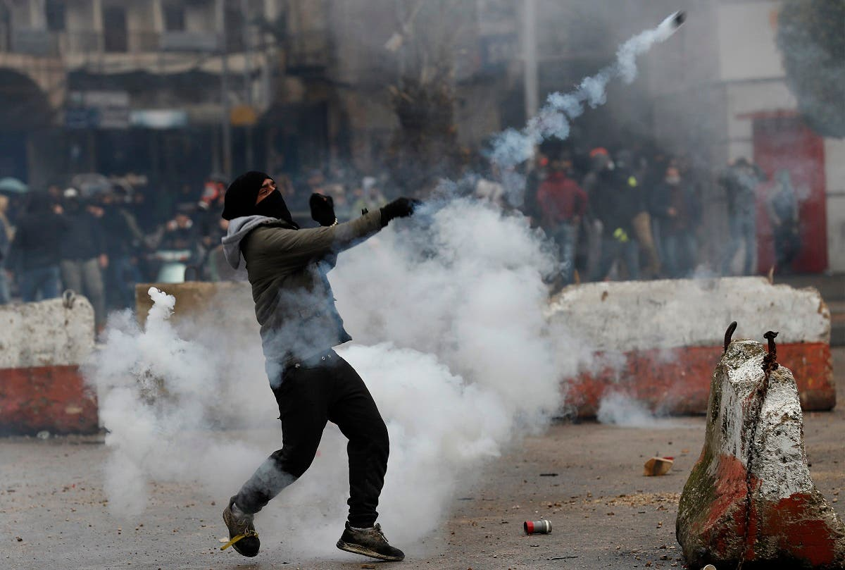 A protester throws back a tear gas canister towards riot policemen during a protest in Tripoli. (AP)