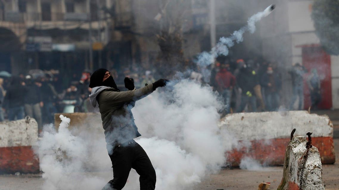 A protester throws back a tear gas canister towards riot policemen during a protest against deteriorating living conditions and strict coronavirus lockdown measures, in Tripoli, Jan. 28, 2021. (AP)