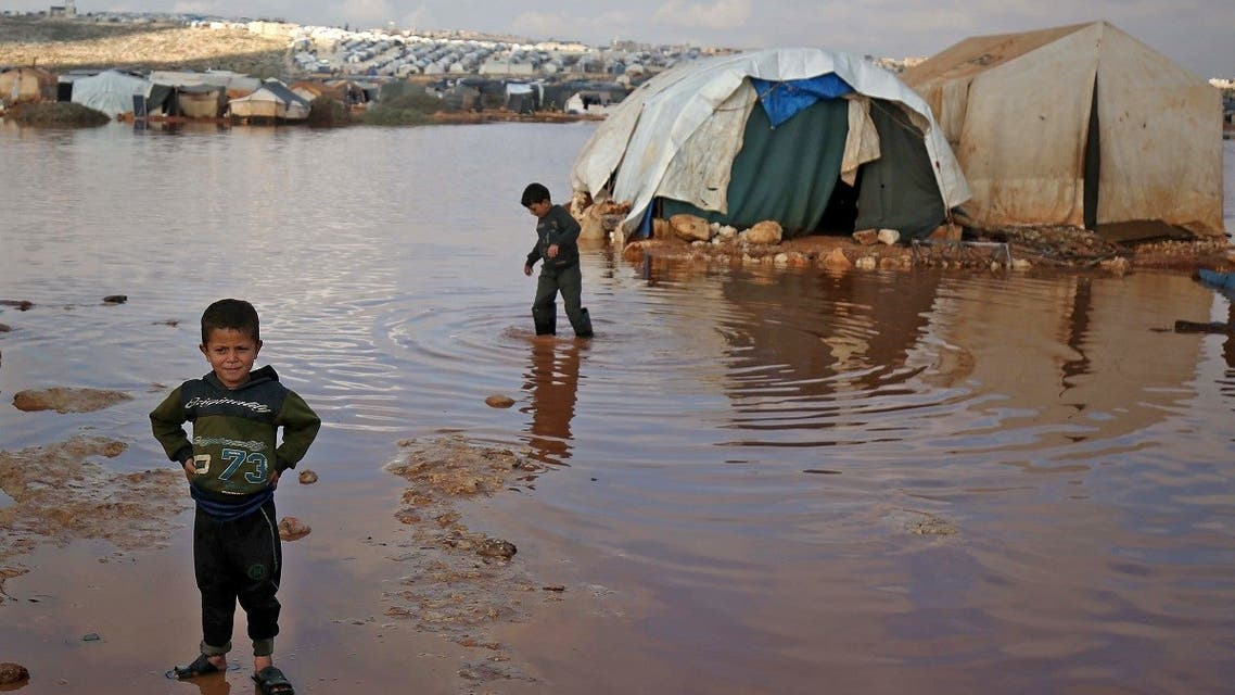 Syrian children play among flooded tents at a camp for displaced Syrians near the town of Kafr Lusin by the border with Turkey, Jan. 19, 2021. (AFP)