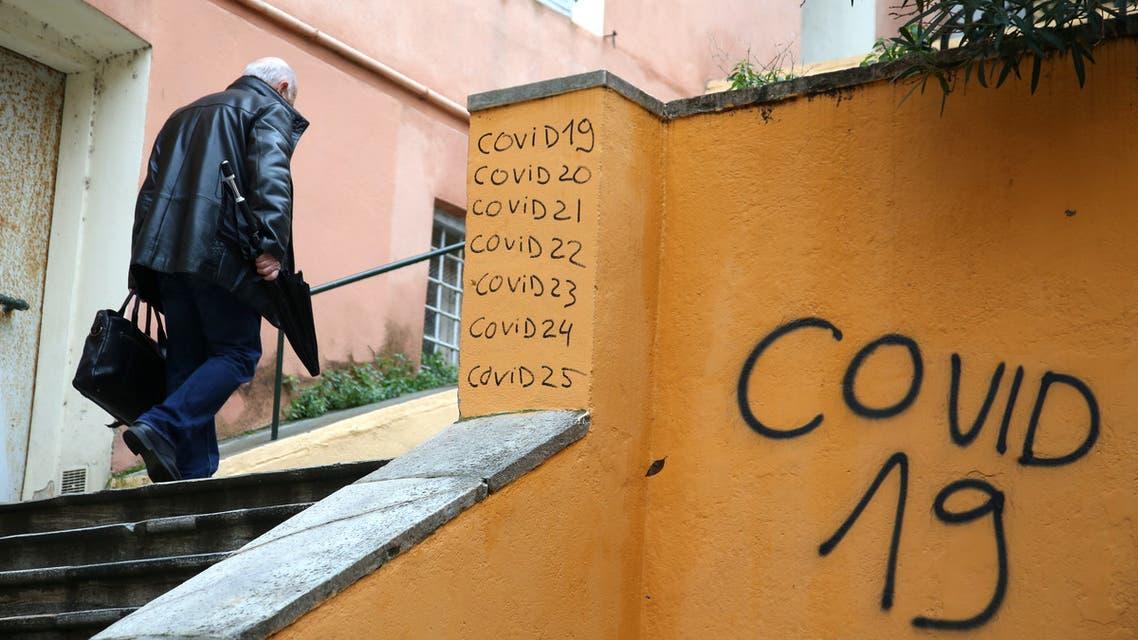 man walks up public stairs past graffiti relating to the coronavirus (COVID-19). (AFP)