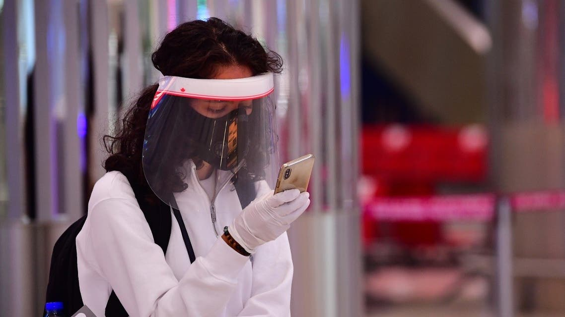 A tourist checks her phone as she wait to get a medical screening upon arrival at Teminal 3 at Dubai airport. (AFP)