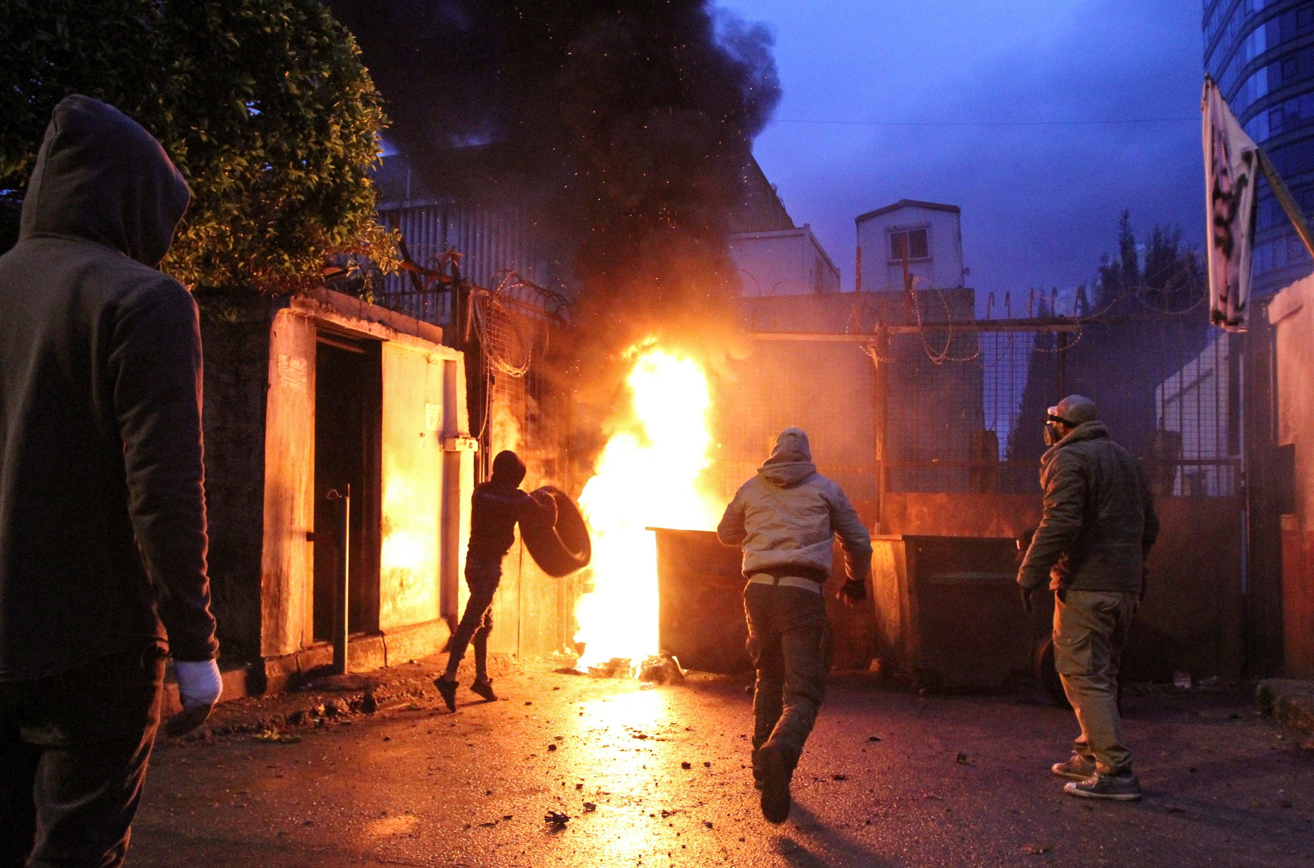 Demonstrators set fire near the government Serail building, during a protest in Tripoli. (Reuters)