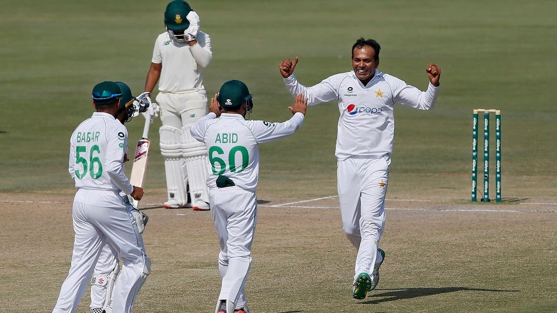 Pakistan's spinner Nauman Ali, right, celebrates with teammates after taking the wicket of South Africa's Temba Bavuma during the fourth day of the first cricket test match between Pakistan and South Africa at the National Stadium, in Karachi, Pakistan, on January 29, 2021. (AP)