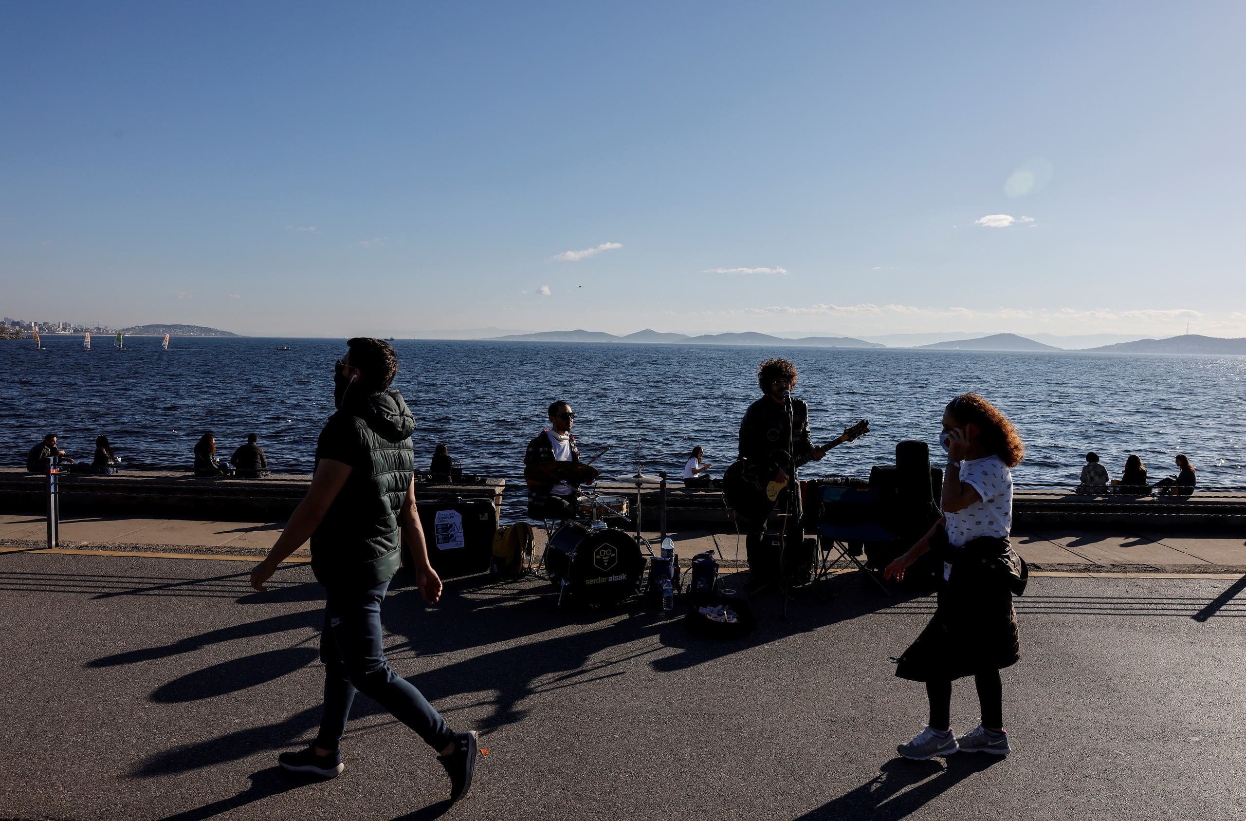 جوانان در استانبول در کنار دریا موسیقی می نوازند