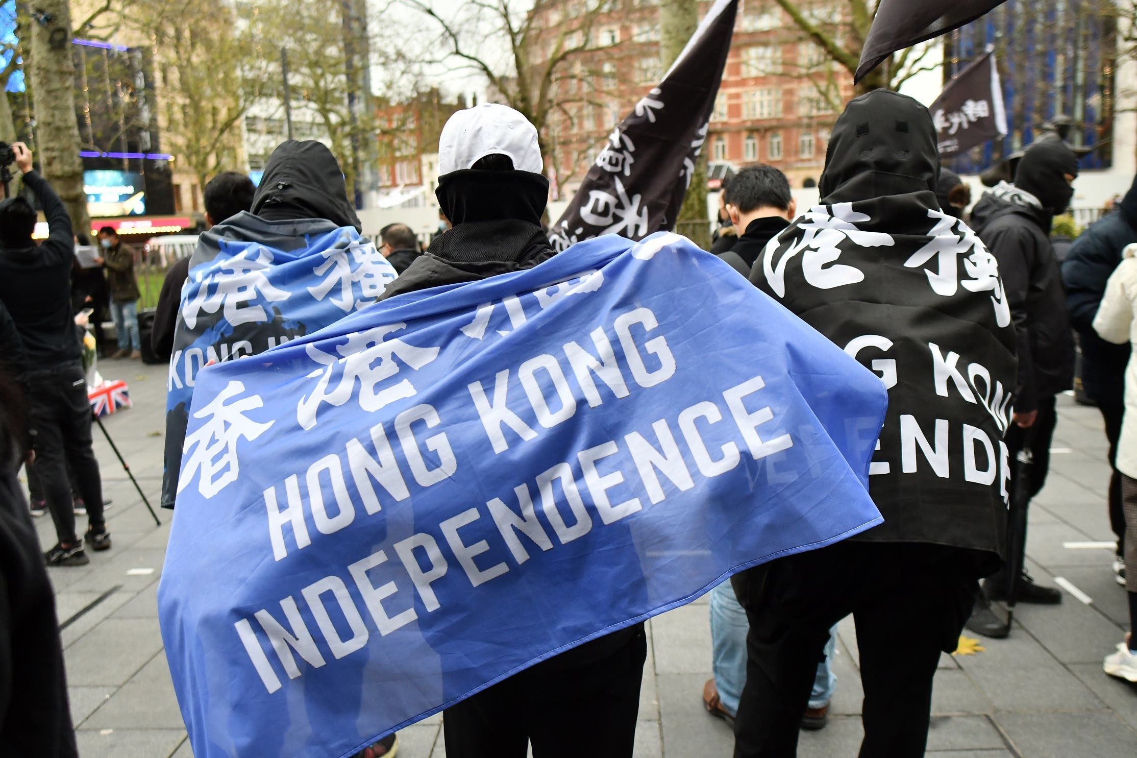 Protesters gather with banners at an event organized by Justitia Hong Kong to mourn the loss of Hong Kong's political freedoms, in Leicester Square, central London on December 12, 2020. (Justin Tallis/AFP)