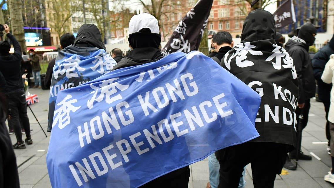 Protesters gather with banners at an event organised by Justitia Hong Kong to mourn the loss of Hong Kong's political freedoms, in Leicester Square, central London on December 12, 2020. Britain expressed alarm on Friday after Hong Kong media tycoon and Beijing critic Jimmy Lai, who has UK citizenship, became the most high-profile figure yet charged under a sweeping national security law.