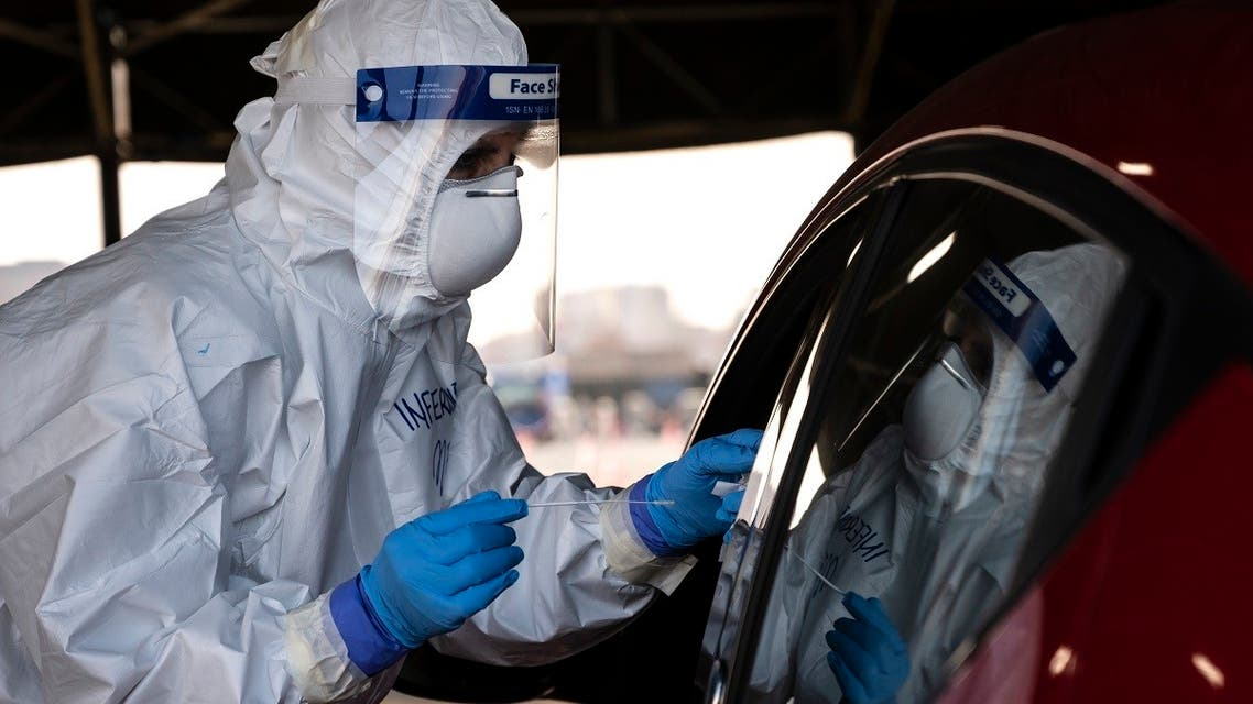 A military medical worker collects on January 12, 2021 a swab sample from a person going through a drive-in swab testing center for COVID-19 set up by the army on the parking lot of the Juventus stadium in Turin, Italy. (Marco Bertorello/AFP)