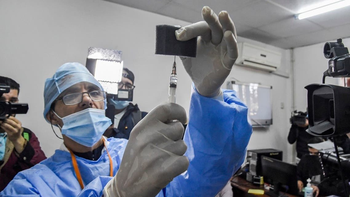 Journalists huddle around a medic about to administer a dose of Russia's Sputnik V vaccine at a clinic in the city of Blida, southwest of the Algerian capital, January 30, 2021. (Ryad Kramdi/AFP)