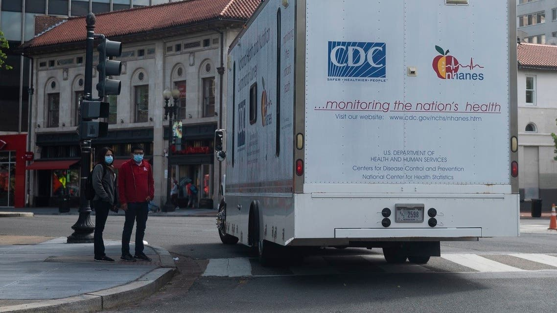 Two people wearing masks wait to cross a street as a truck from the Center for Disease Control (CDC) pass by in Washington, DC on May 21, 2020. (Andrew Caballero-Reynolds/AFP)