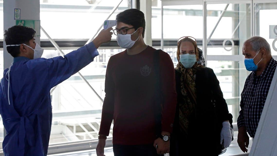 An airport worker checks the body temperature of incoming passengers upon arrival at the Iranian capital Tehran's Imam Khomeini International Airport on July 17, 2020. (AFP)
