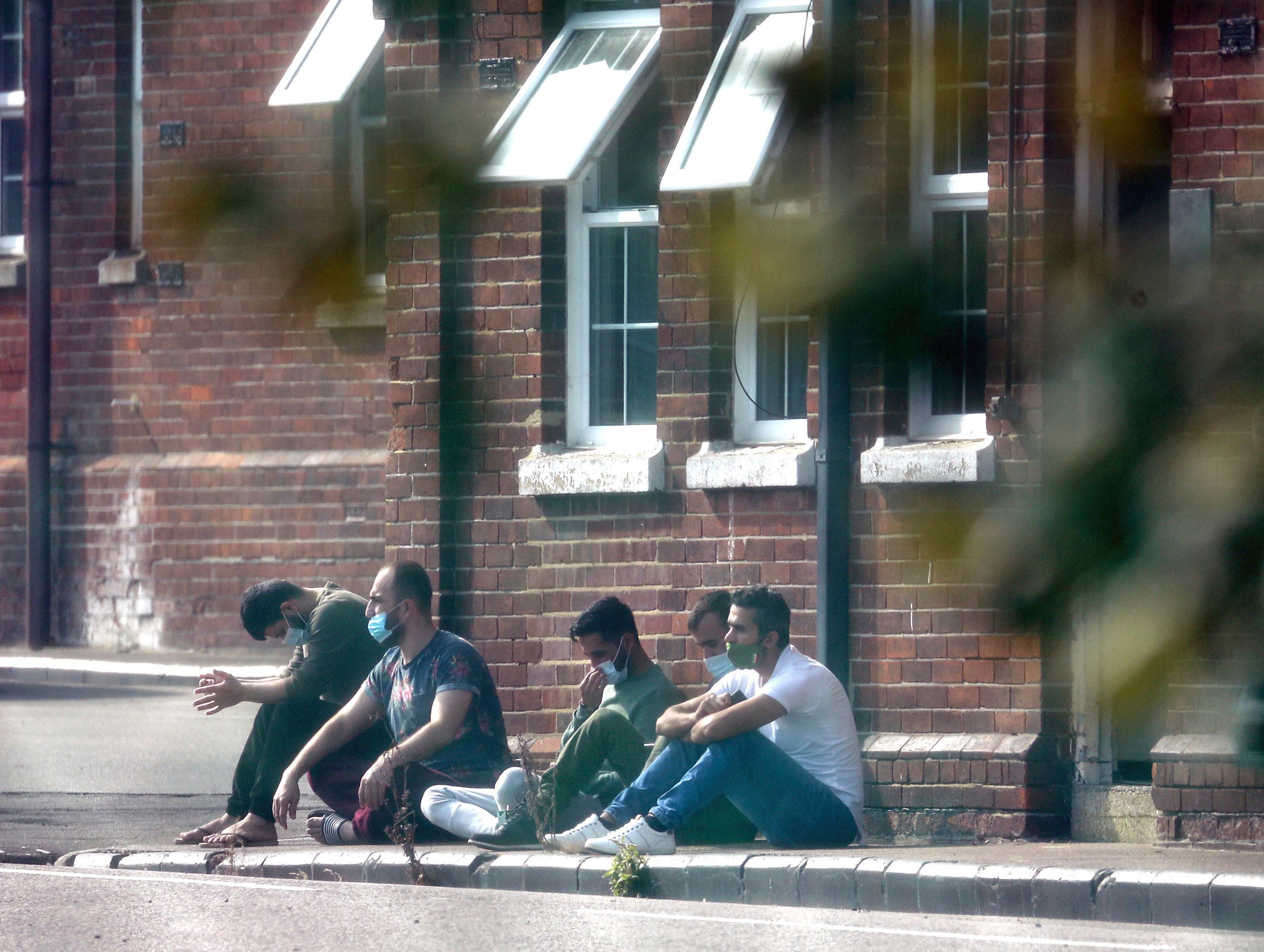 A group of men, thought to be migrants, sit outside in the sunshine after arriving on Monday, at Napier Barracks in Folkestone, Kent, England, Tuesday, Sept. 22, 2020. Migrants will be housed in the military barracks from this week while their asylum claims are processed. (Gareth Fuller/PA via AP)