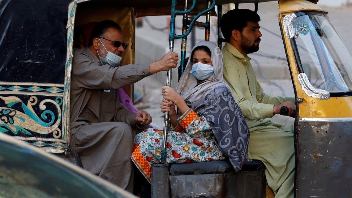 People with masks against COVID-19 travel by rikshaw (tok tok) in Karachi, Pakistan January 25, 2021. (Reuters/Akhtar Soomro)