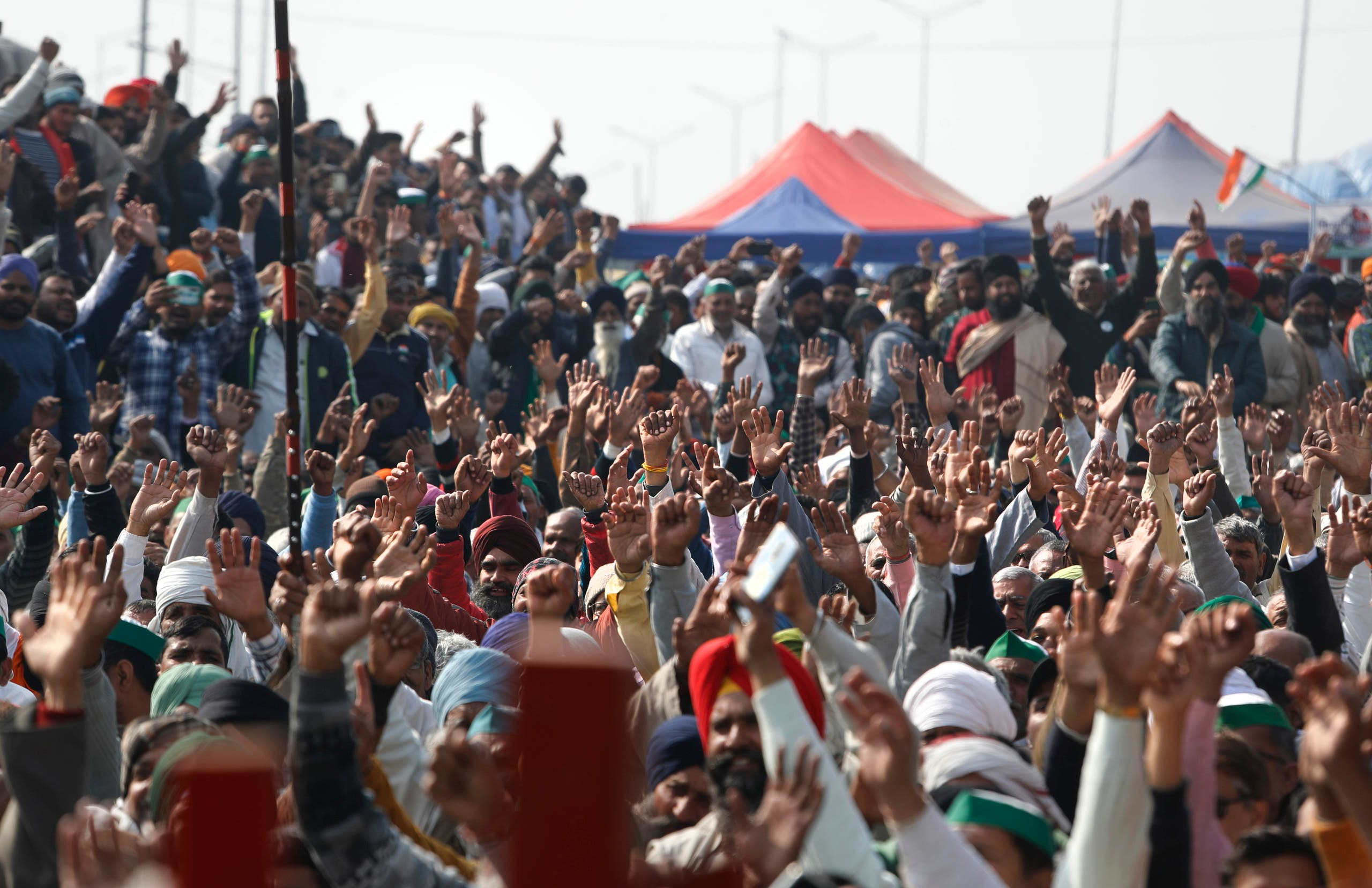Farmers raise their hand as they shout slogans during a day-long hunger strike to protest against new farm laws, at the Delhi-Uttar Pradesh border, on the outskirts of New Delhi, India on Jan. 30, 2021. (AP)