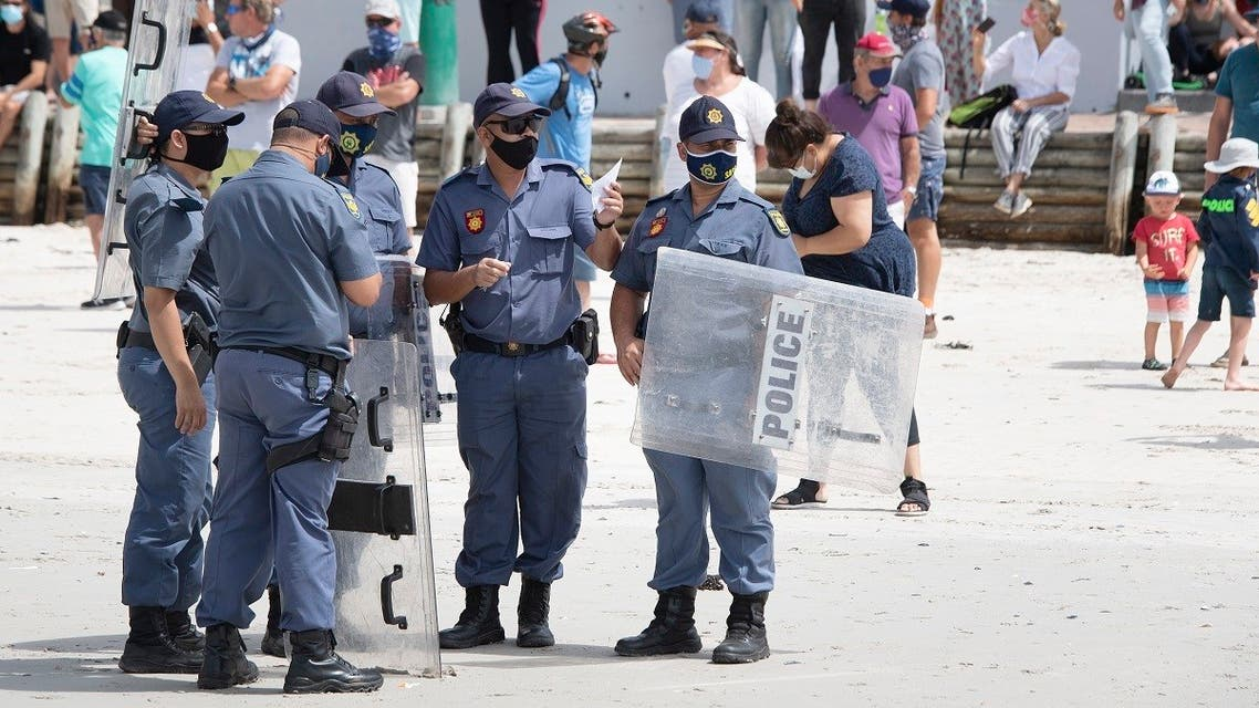 Members of the South African Police Services with riot shields patrol during a coronavirus-protest against the government's ban on people enjoying the beach in Cape Town's Muizenberg district on January 30, 2021. (Rodger Bosch/AFP)