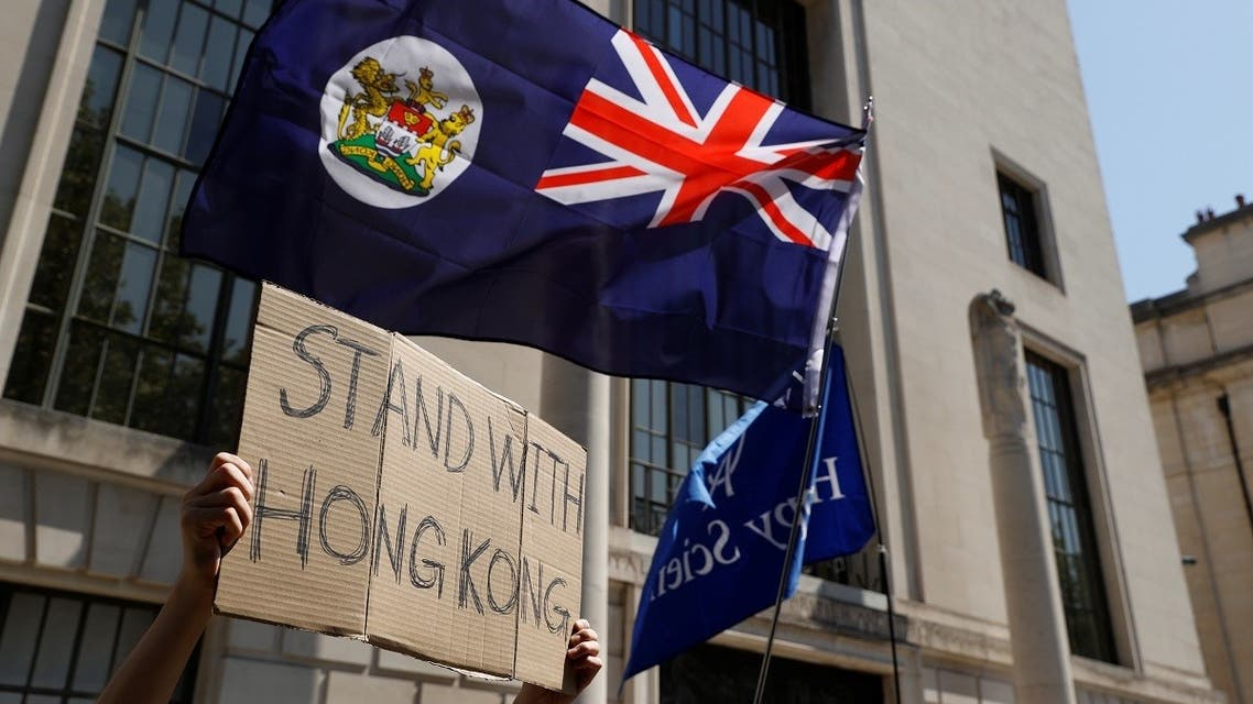 A flag of Hong Kong is waved in front of a placard during a protest against Hong Kong's deteriorating freedoms outside China's embassy, in London, Britain, July 31, 2020. (Reuter/John Sibley)